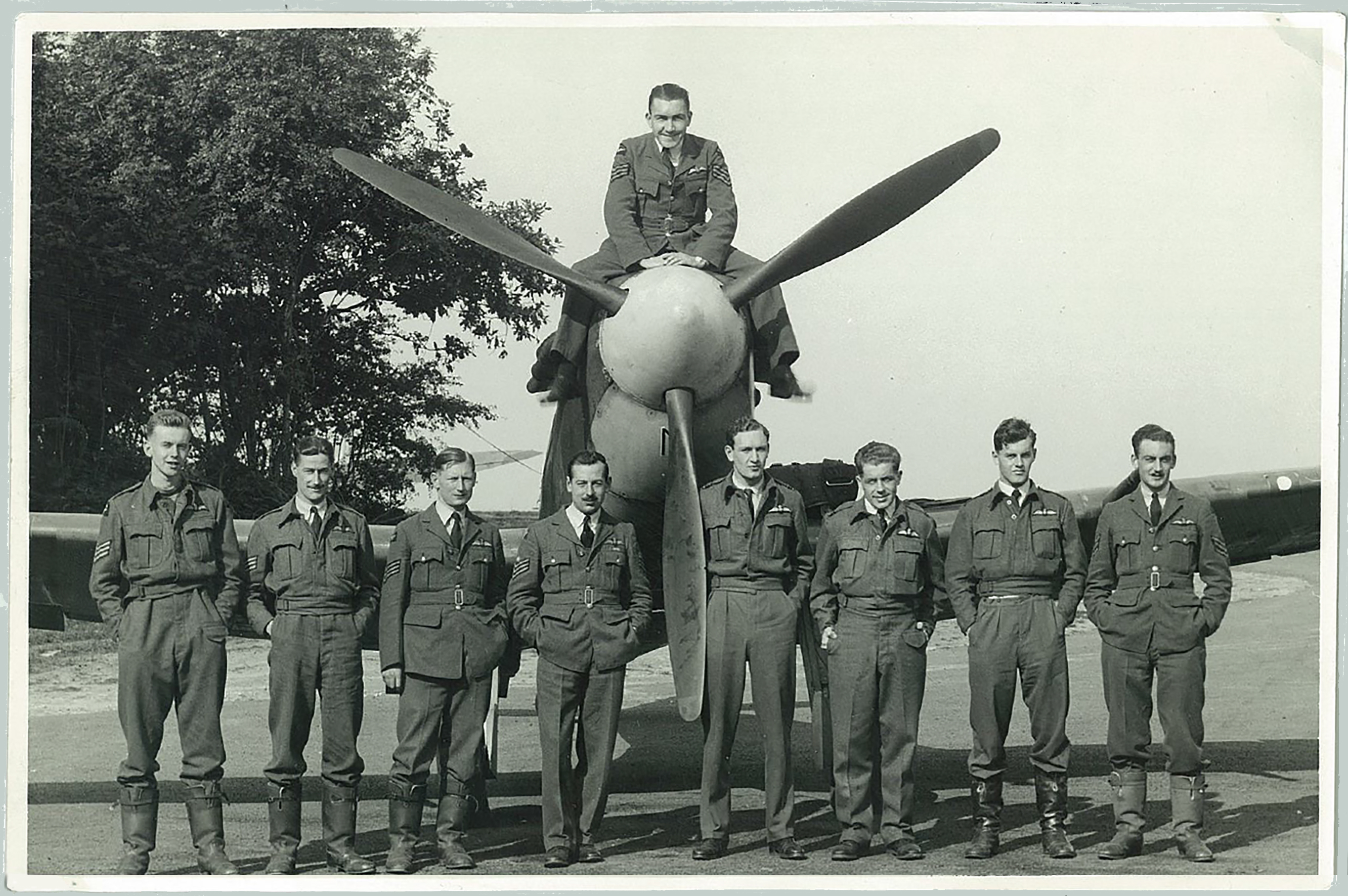 With one of their Supermarine Spitfires, Flying Officer John Stewart Hart (fourth from right) and other members of No. 602 Squadron gather for a photograph in Westhampnett, England, during the Battle of Britain.