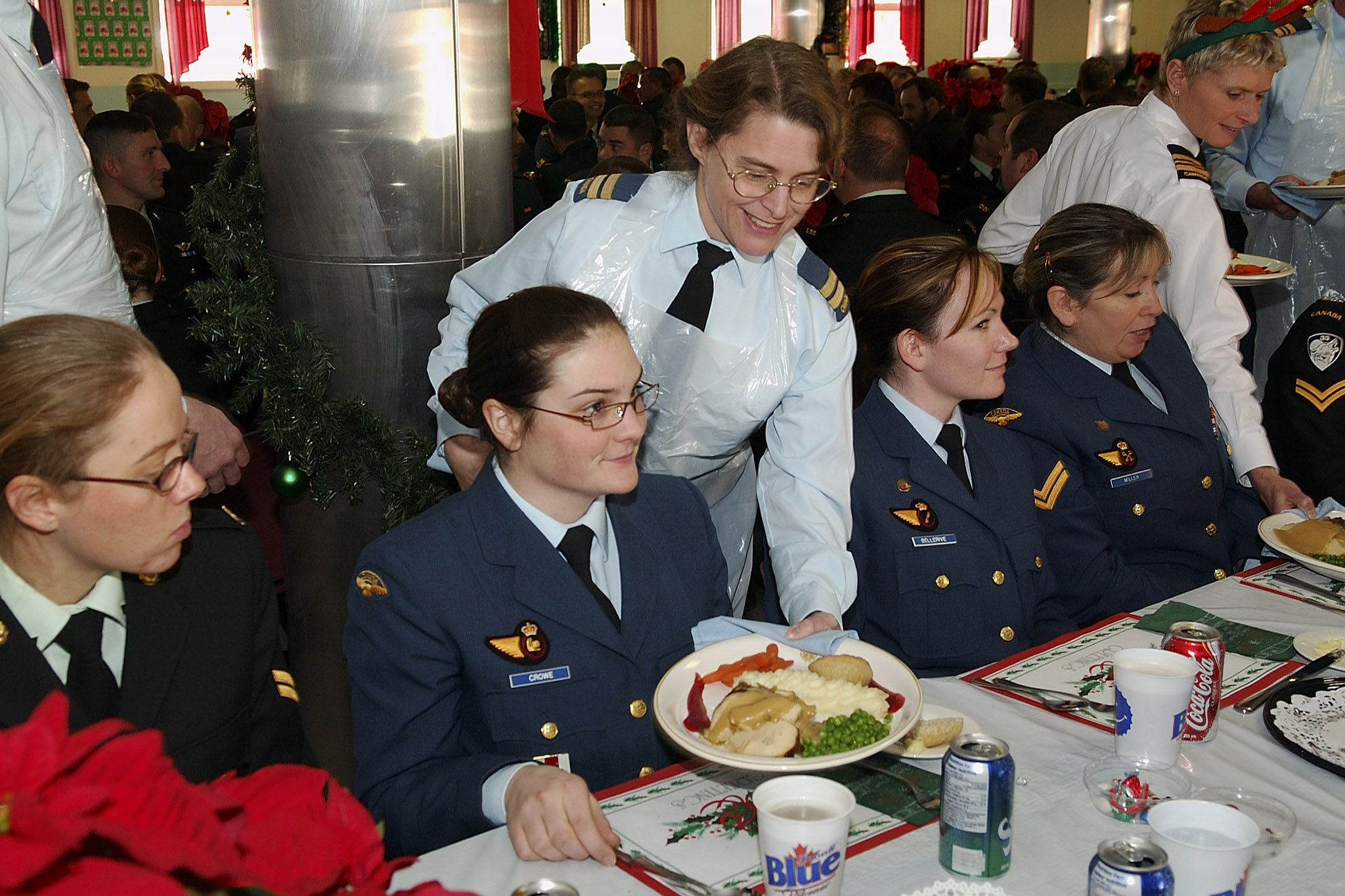 The tradition of the senior personnel serving the junior personnel continues to this day. Here Captain Pauline Quaghebeur serves Aviator Samantha Crowe during the Canadian Forces Support Training Group Christmas dinner at Canadian Forces Base Borden on December 12, 2005. PHOTO: Sergeant Daren Kraus