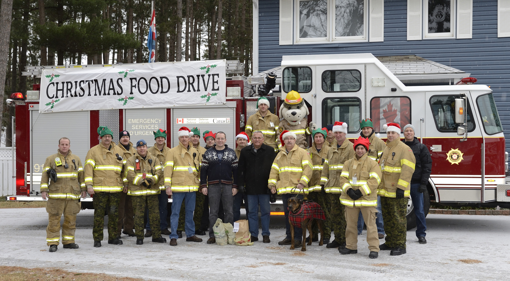 Firefighters from 14 Wing Greenwood, Nova Scotia, along with Sparky the fire dog, begin the 2014 Christmas Food Bank Drive by visiting Colonel Iain Huddleston (centre left), commander of 14 Wing, and Chief Warrant Officer Pierrot Jetté, wing chief warrant officer (centre right). The Food Bank Drive is an annual event that provides much-needed food stuffs to local food banks in the Annapolis Valley. PHOTO: Corporal Don Kirkwood