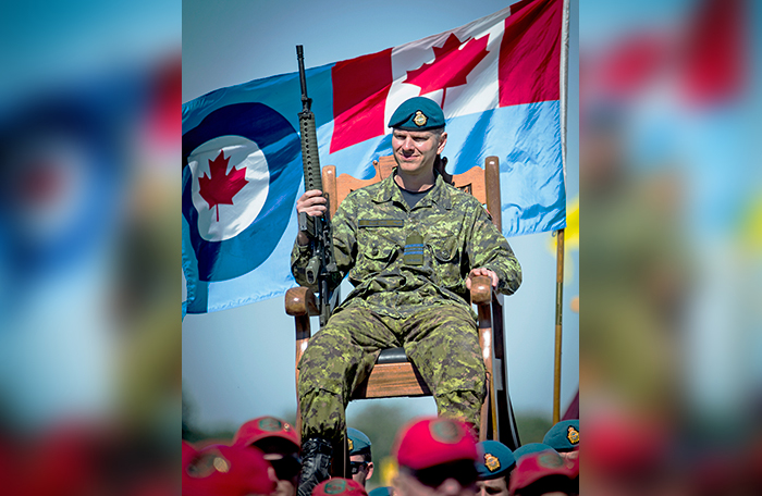 slide - A man in Canadian combat clothing, wearing an RCAF blue beret, is carried in a chair on the shoulders of other people. An RCAF flag waves behind him.