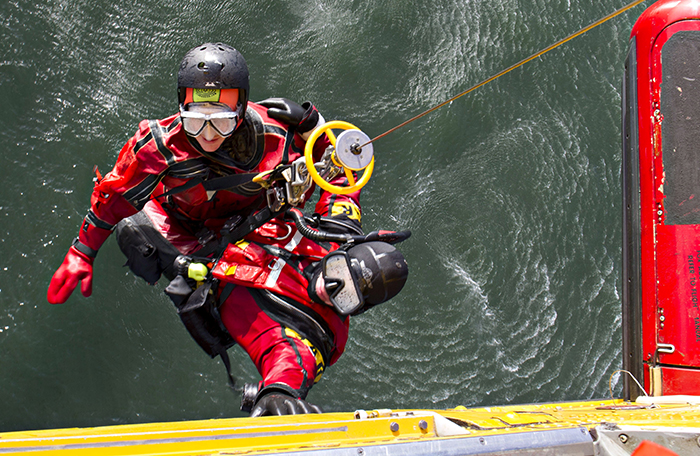slide - Two technicians are suspended over water from a helicopter