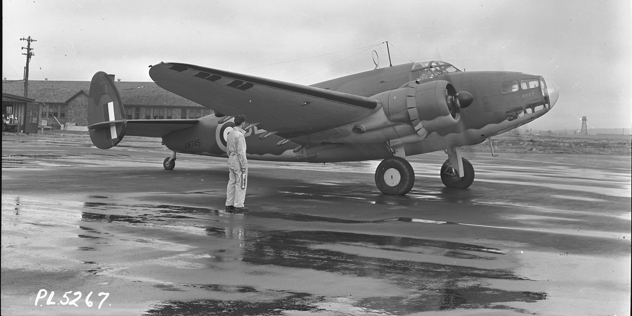 An old black and white photo of a large propeller-drive aircraft.