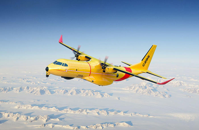 slide - A large yellow aircraft flies over snow-covered terrain.