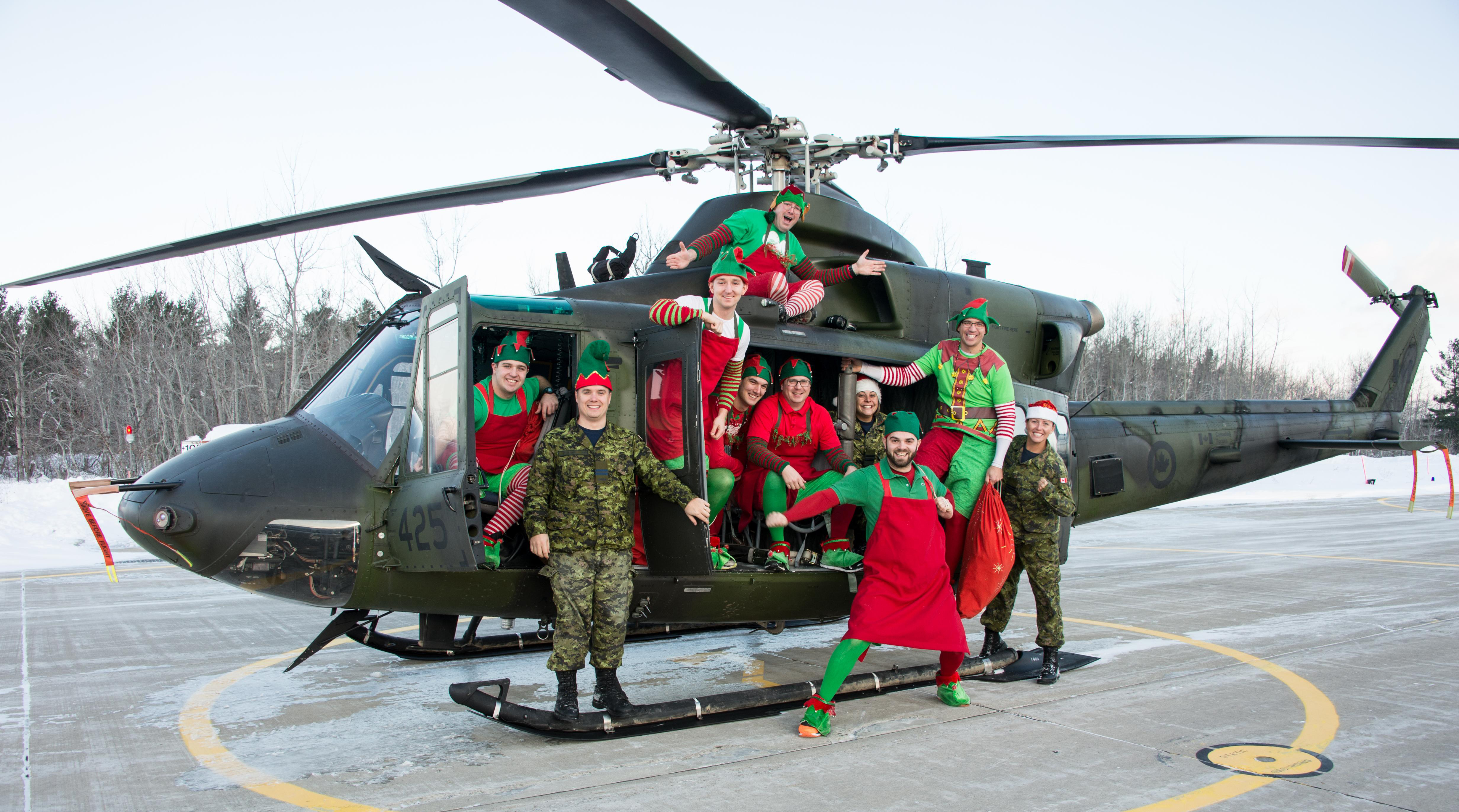 """Elves"" from 400 Tactical Helicopter Squadron, located at Canadian Forces Base Borden, Ontario, load a CH-146 Griffon helicopter with toys bound for the Hospital for Sick Children during Operation Ho Ho Ho on December 14, 2016. The initiative to bring holiday cheer to children who must be in SickKids Hospital over the Christmas season has been running for 13 years. From left to right are Aviator Paul Wilson, Captain Jeffery Pollard, Ordinary Seaman Christopher Anderson, Corporal Martin Hamel, Aviator William Rittershofer, Master Corporal Jason Merner, Major Laura Laycock, Aviator Daniel Rodrigues, Corporal Jesse MacIlroy and Captain Karmen Hill. PHOTO: Corporal Lindsay Neifer, CB18-2016-0627-003"