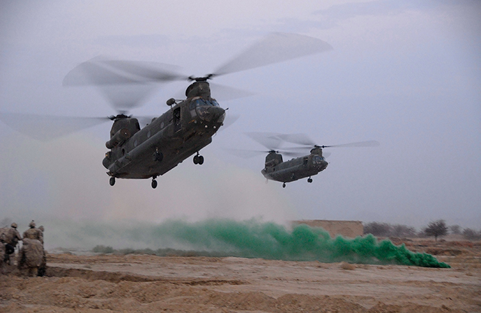 slide - Two helicopters prepare to set down as a green flare smokes and five men in desert camouflage watch.