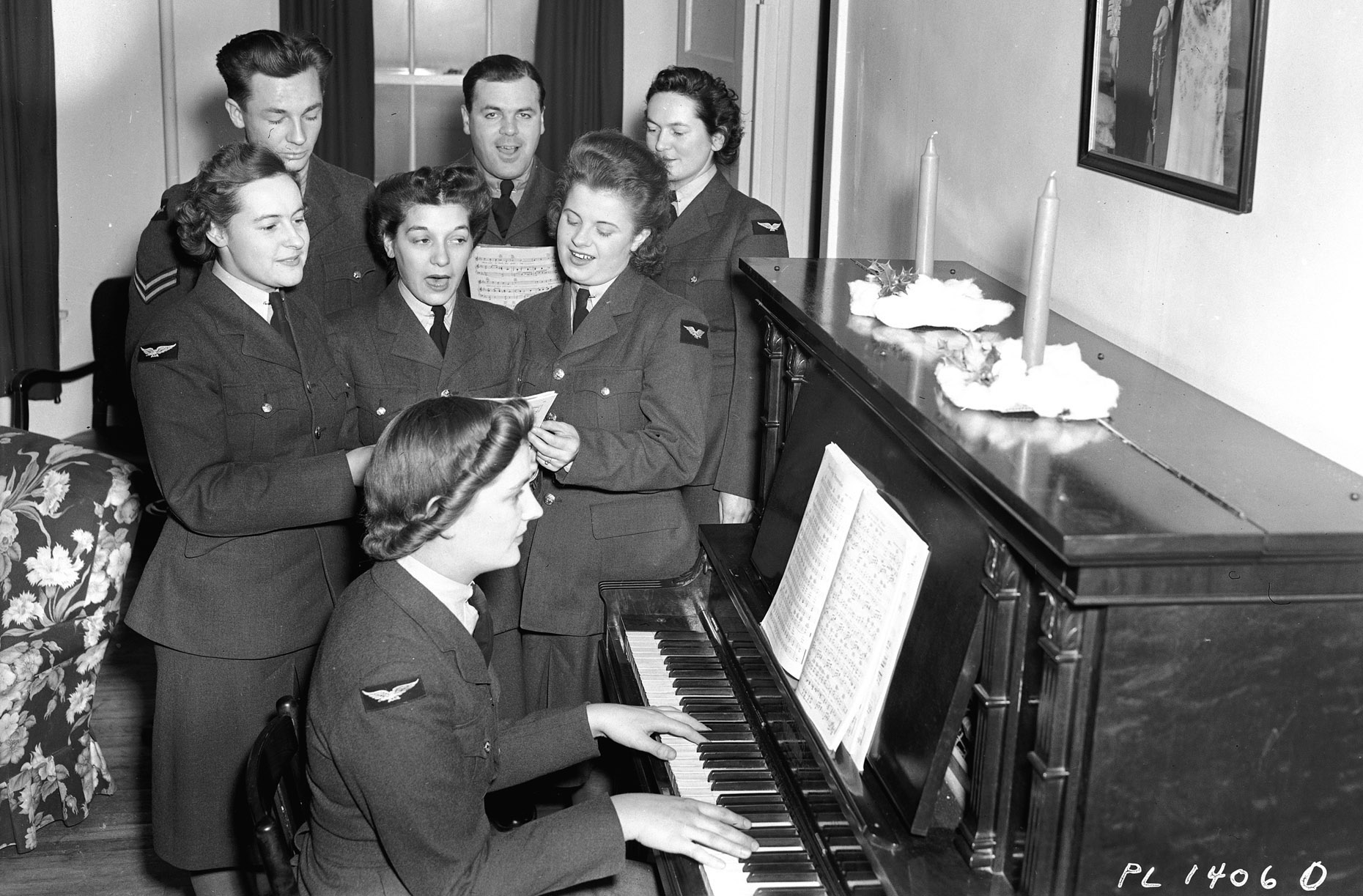 Airwomen (members of the RCAF's Women's Division) and airmen sing Christmas carols at No. 7 Manning Depot, Rockcliffe, Ottawa, on December 21, 1942. Back row, left to right: Corporal E. Trainer, North Augusta, Ontario; Flight Sergeant R.D. McDonald, London, Ontario; Aircraftwoman 2nd Class M.T. Houston, Montreal, Quebec. Front row, left to right:  Aircraftwoman 2nd Class H.G. Wheeler, Weston; Aircraftwoman 2nd Class M.N. DeFrancis, Montreal, Quebec; Aircraftwoman 2nd Class J.B. Watson, Winnipeg, Manitoba, and, at the piano, Aircraftwoman 1st Class Ella McMahon, Killal, Alberta.. PHOTO: DND Archives, PL-14060