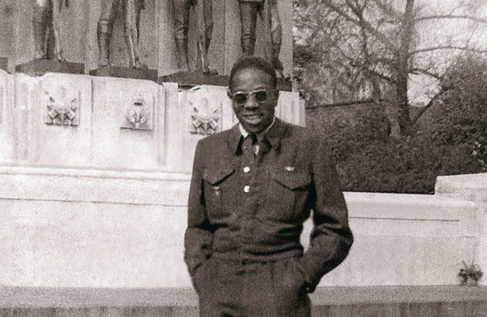 slide - A vintage black and white photo of a man in a military uniform standing in front of a commemorative monument
