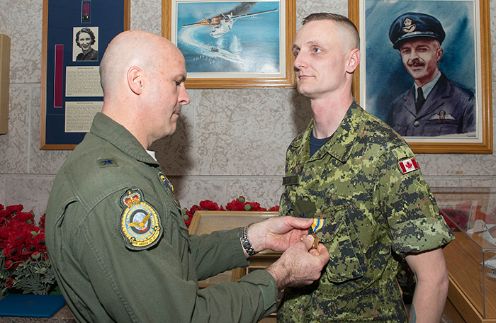 slide - A man in a green flight suit uniform pins a medal on a man wearing a green disruptive pattern uniform