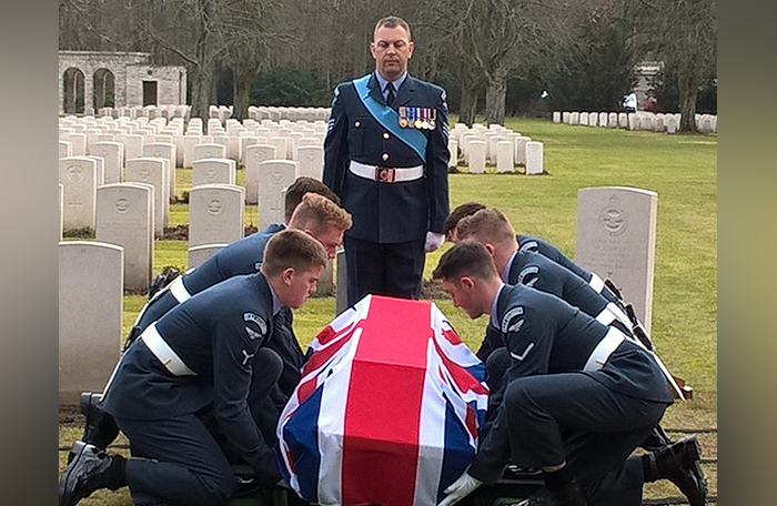 slide - Three men in uniforms crouch on each side of a flag-draped coffin in a graveyard while a seventh stands at the head of the coffin.
