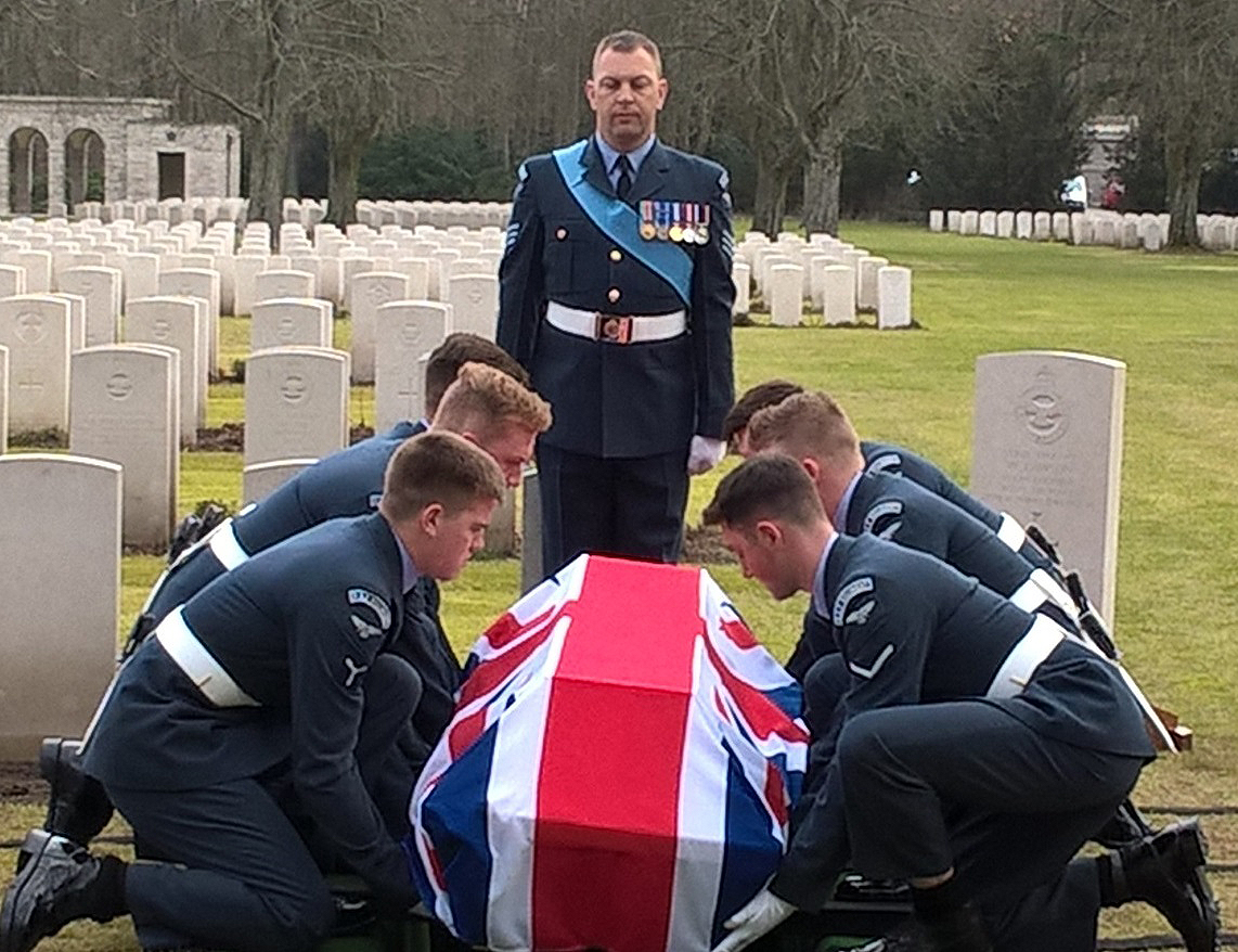 Three men in uniforms crouch on each side of a flag-draped coffin in a graveyard while a seventh stands at the head of the coffin.