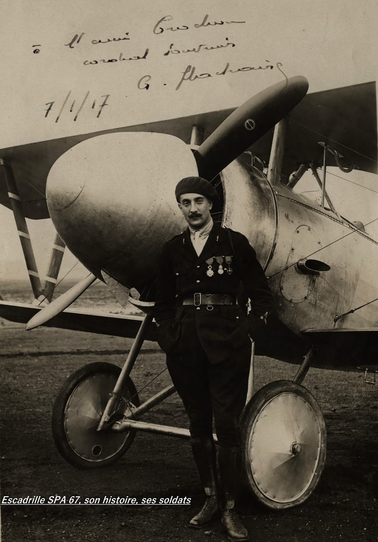 An old photograph of a man wearing a uniform with medals and standing in front of a vintage aircraft.