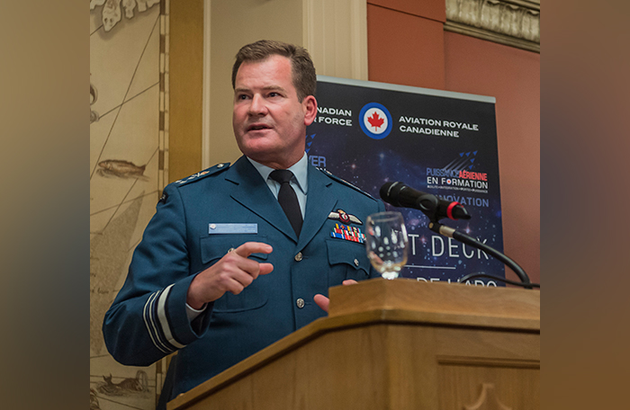 slide - A man in a blue uniform stands at a lectern, talking.