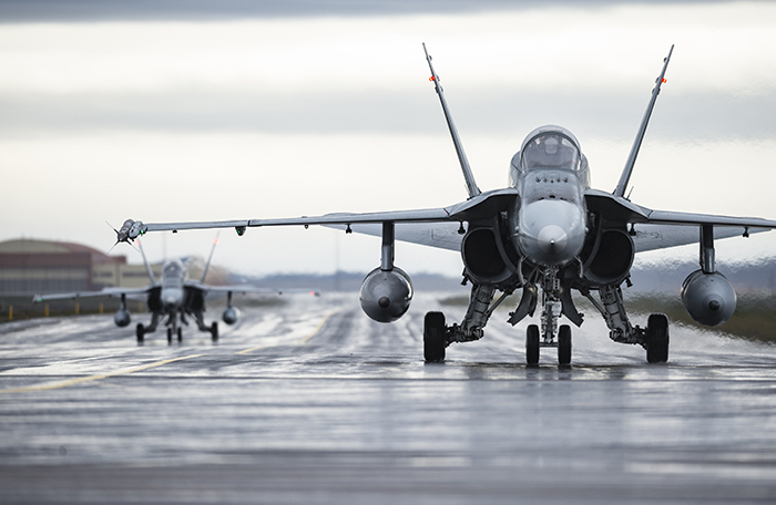 slide - Two grey fighter aircraft approach the camera on a wet tarmac.