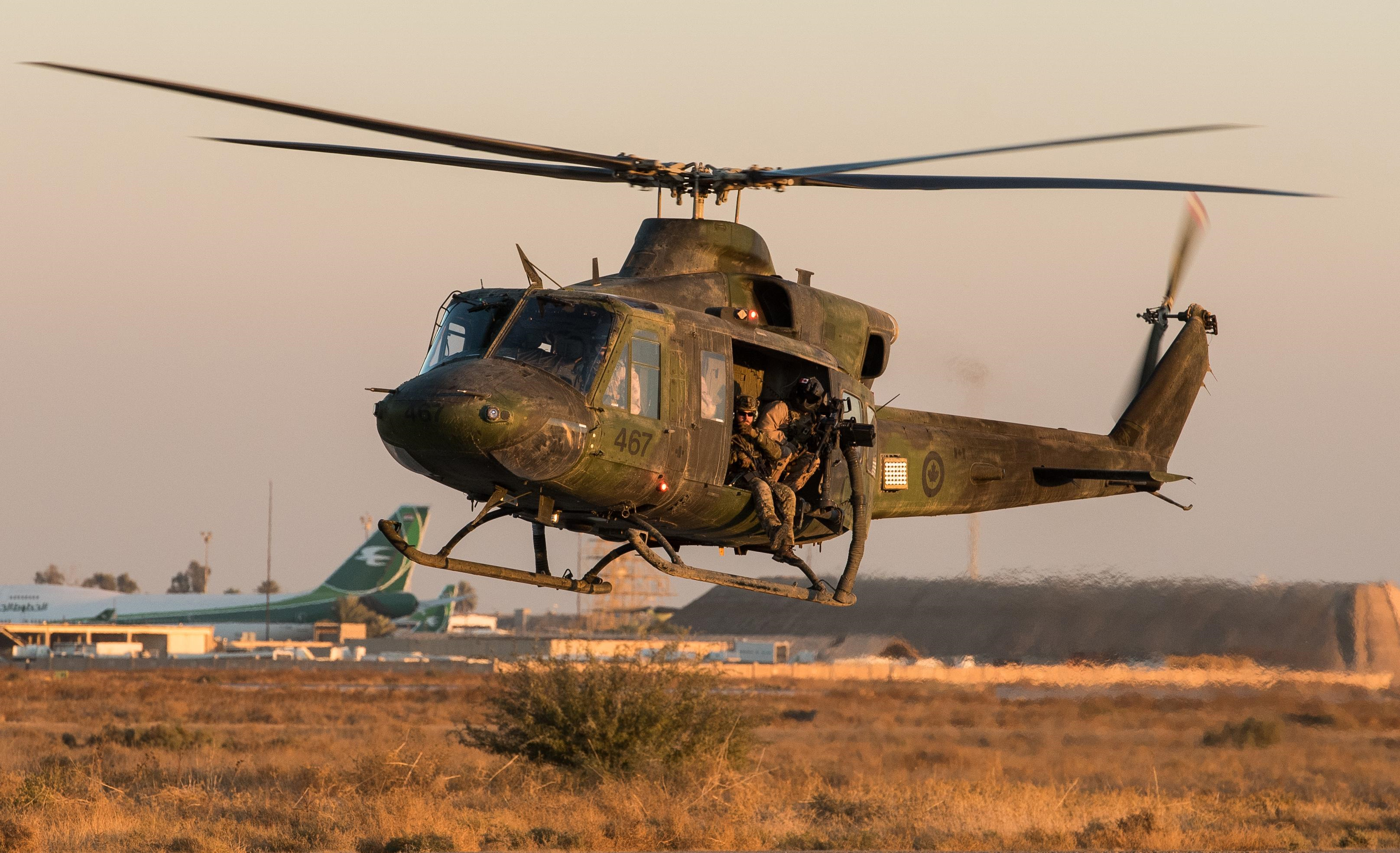A green and black military helicopter lifts off from the tarmac. Armed soldiers wearing green camouflage uniforms sit in the open side door.