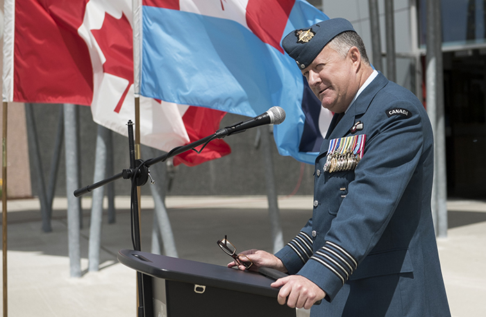 slide - A side view of a man in a blue air force uniform, stands behind a podium outdoors, with flags flying in the background.