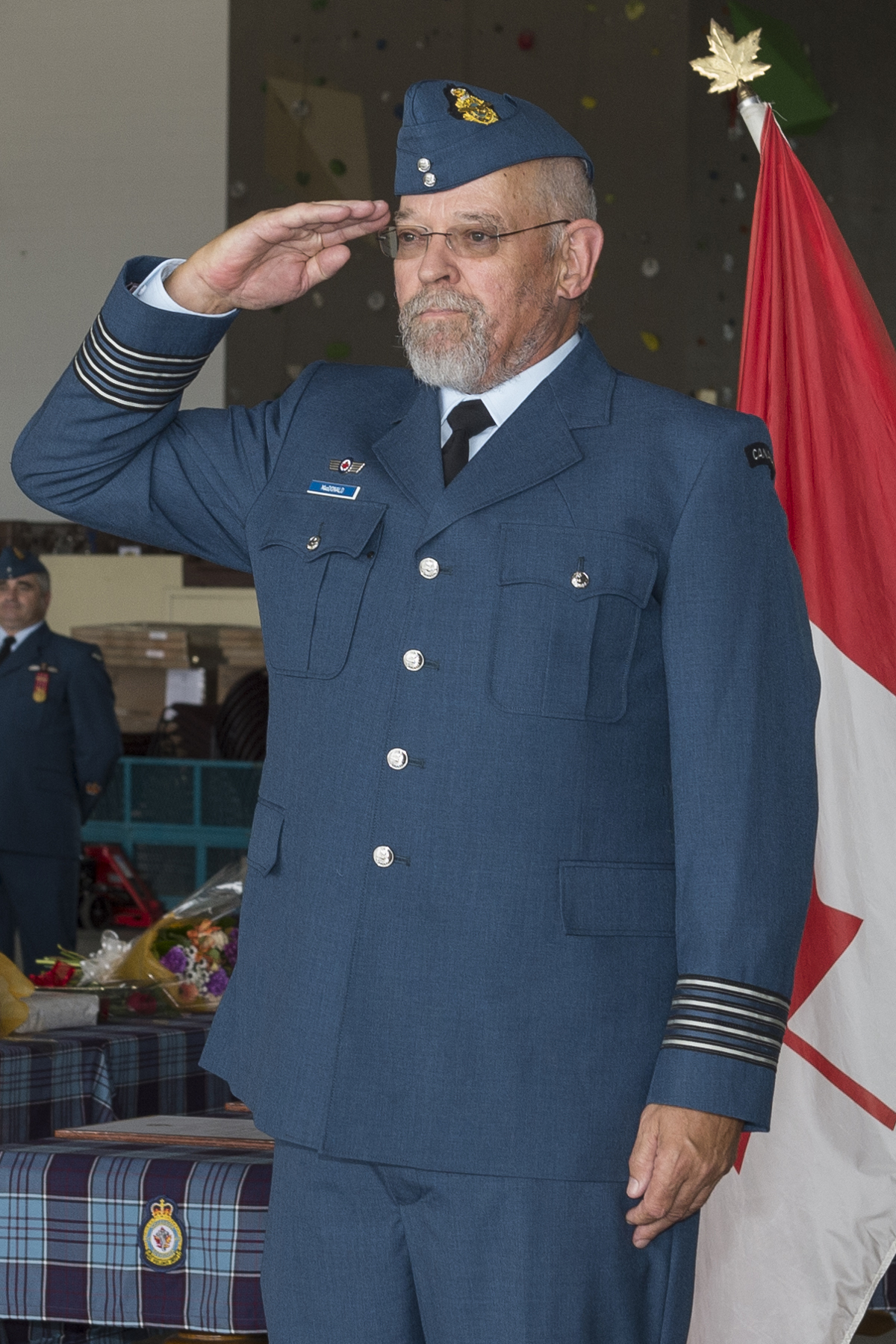 A man in a blue military uniform salutes, flanked by two large images of the badge he wears on his uniform.