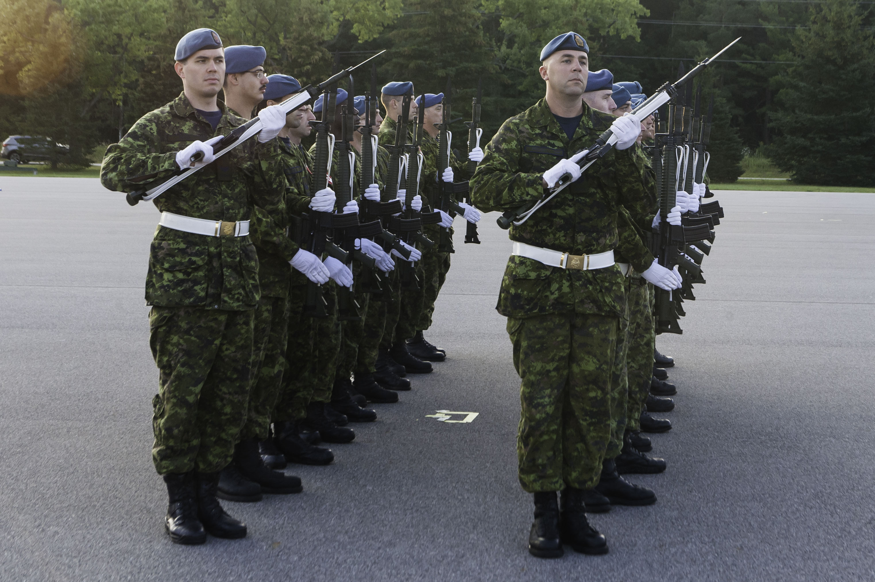 A group of military personnel wearing white gloves and carrying rifles.