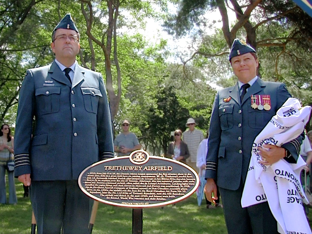 A man and a woman, both wearing blue air force uniforms, stand on either side of a brass plaque mounted on post in an outdoor area.