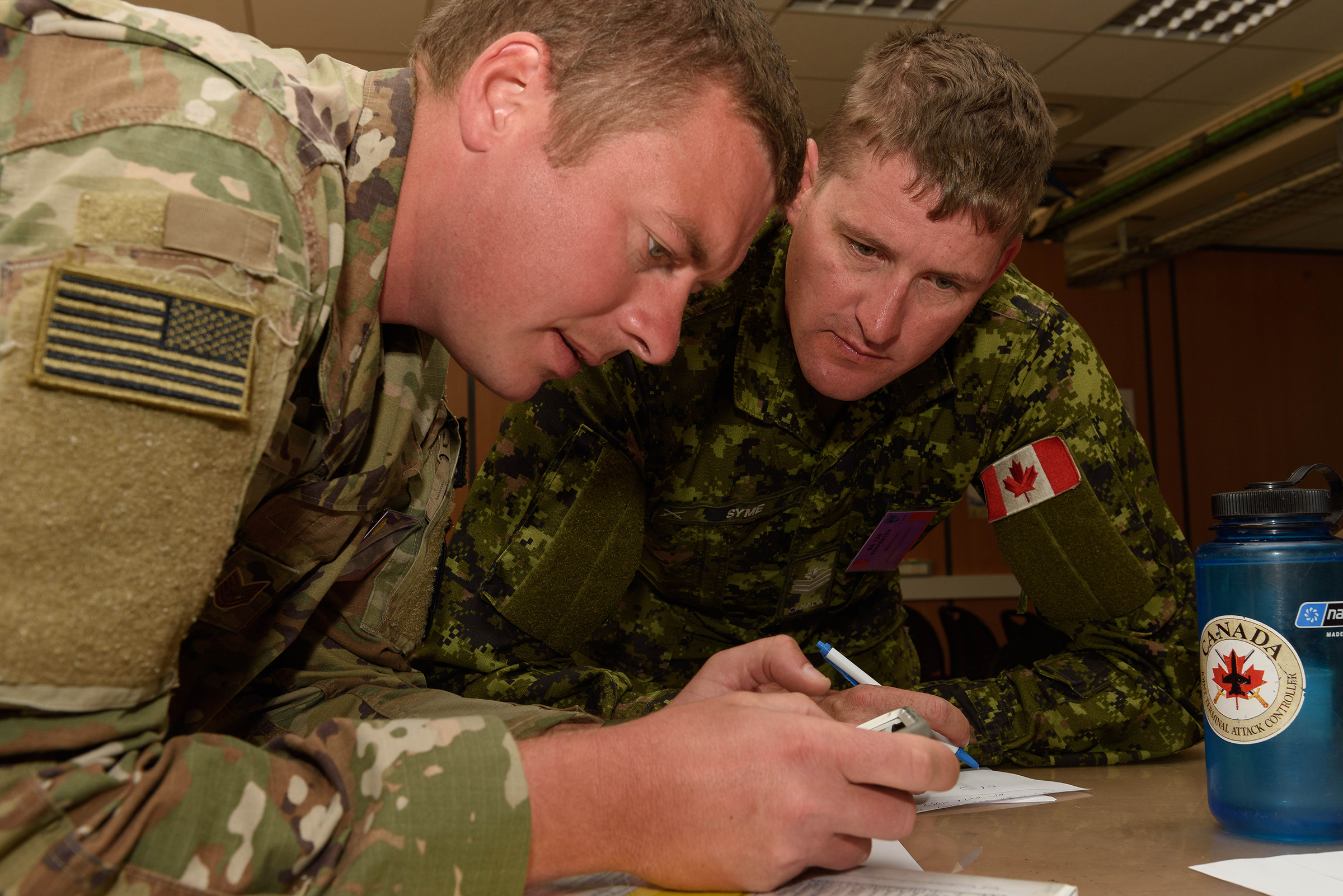 Technical Sergeant Kristopher Faber of the United States and Sergeant Tyler Syme (right), a joint terminal air controller from the Canadian Armed Forces, prepare a mission during SERPENTEX 2017 on September 21, 2017. PHOTO: Master Corporal Louis Brunet, BN53-2017-0005-005
