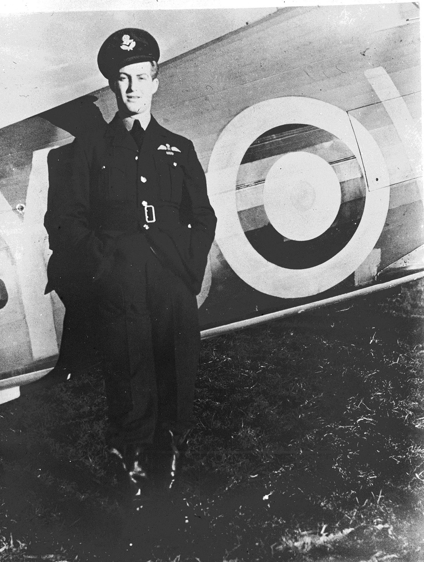 In an undated photograph, 401 Squadron's Flying Officer Blair Dalzell Russel, of Montreal, Québec, leans against the fuselage of his Hawker Hurricane fighter at a Fighter Station somewhere in England. Flying Officer Russel received the Distinguished Flying Cross from King George VI for his service with No. 1 Fighter Squadron of the Royal Canadian Air Force in the battle over Britain, as did Squadron Leader Ernest Archibald McNab and Flight Lieutenant Gordon Roy McGregor. PHOTO: DND Archives, PL-3093