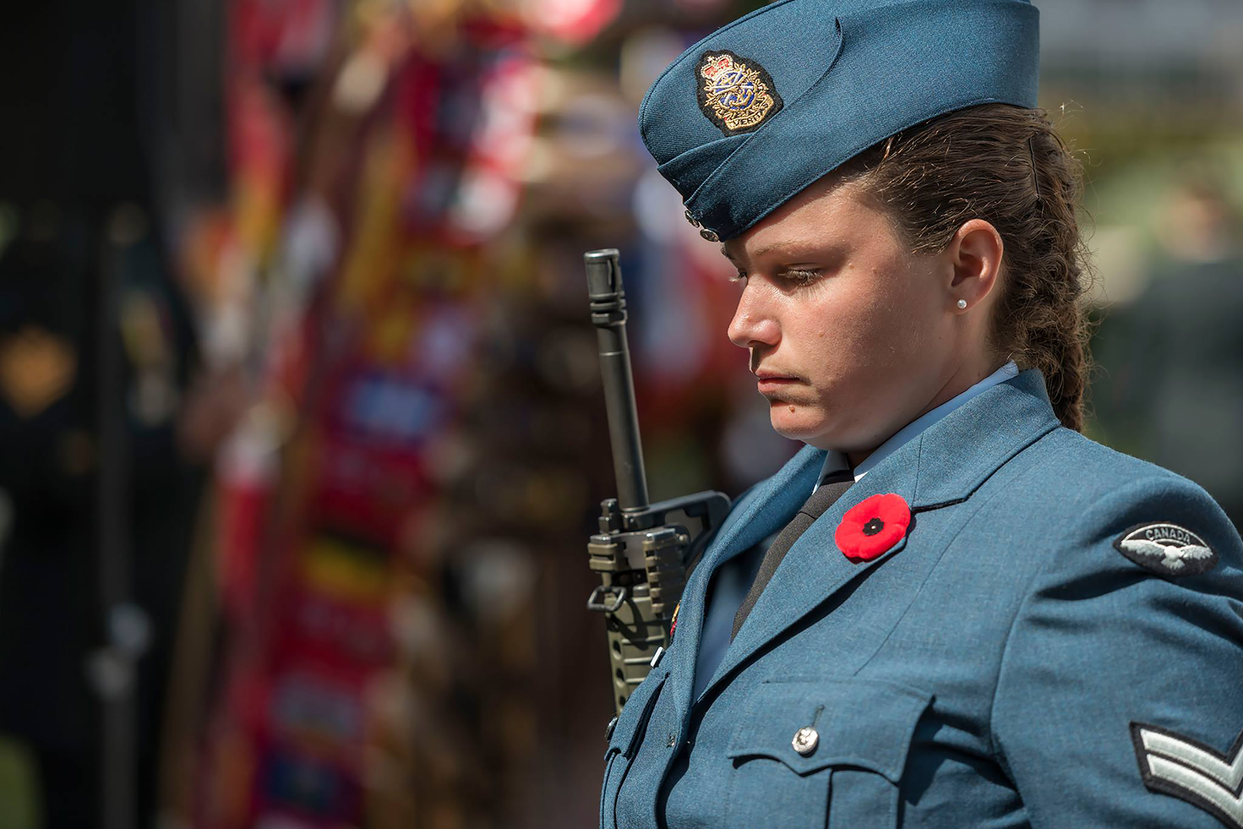 A head-and-shoulders photograph of a young woman in a blue uniform, standing with her head bowed, wearing a red poppy in her lapel and holding an automatic weapon.