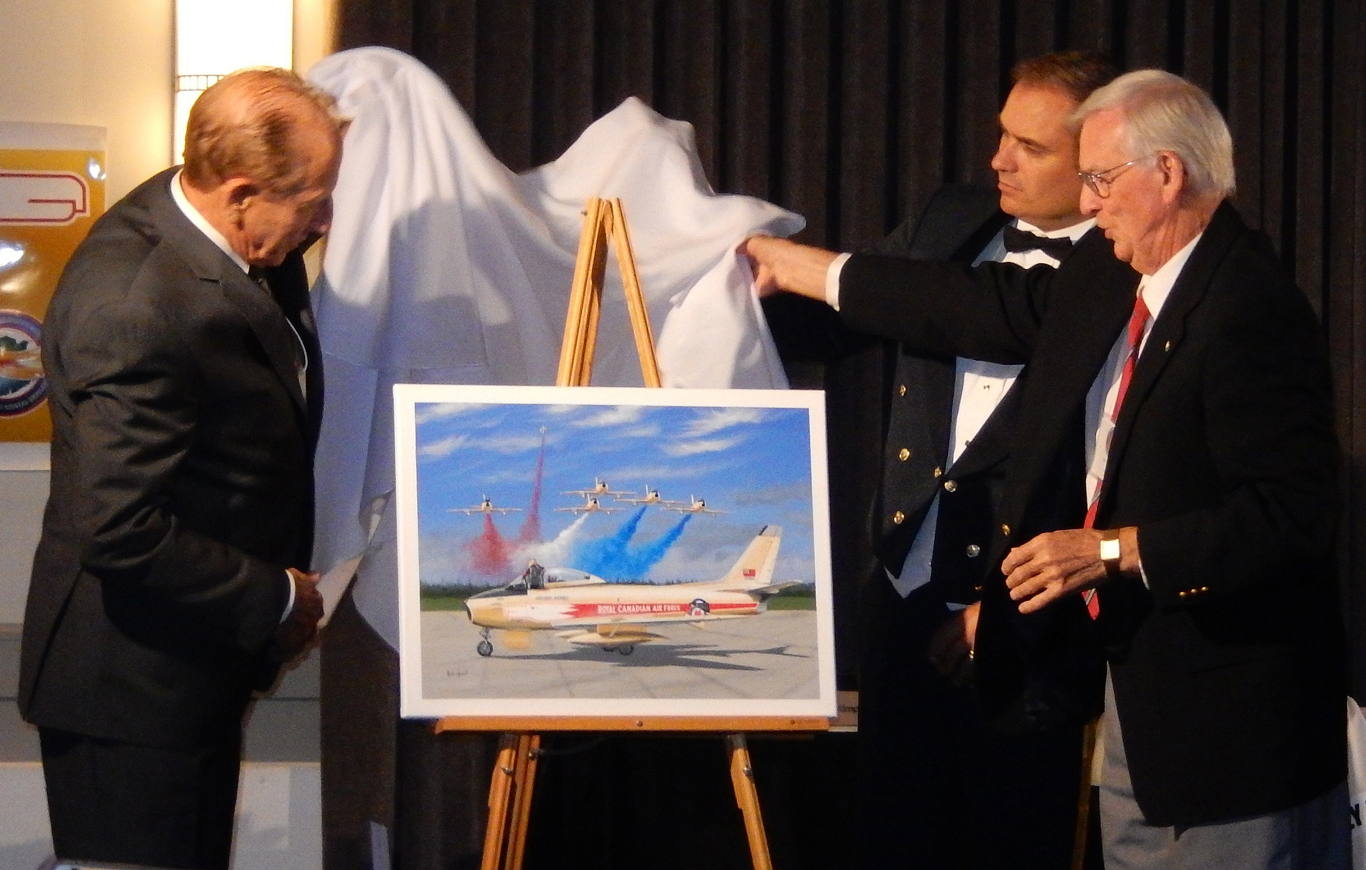 Three men surround an easel on which rests a painting of a golden-coloured aircraft. They are holding the white cloth they have just lifted from the painting.