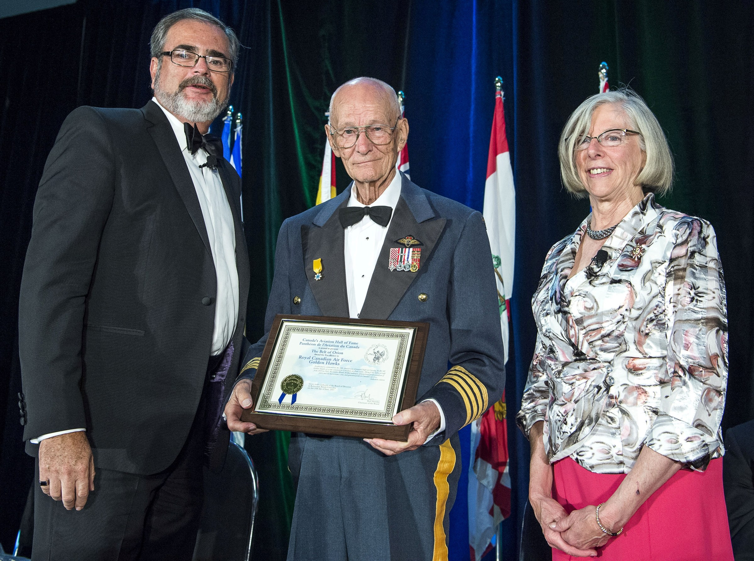 Wing Commander (retired) Fern Villeneuve, centre, accepts the certificate for the Belt of Orion Award of Excellence presented to the Golden Hawks by Canada's Aviation Hall of Fame during the 2017 induction ceremonies. At left is Hall board chairman, Rod Sheridan, with guest speaker and presenter Judith Guichon, the Lieutenant-Governor of British Columbia. PHOTO: © Rick Radell photo