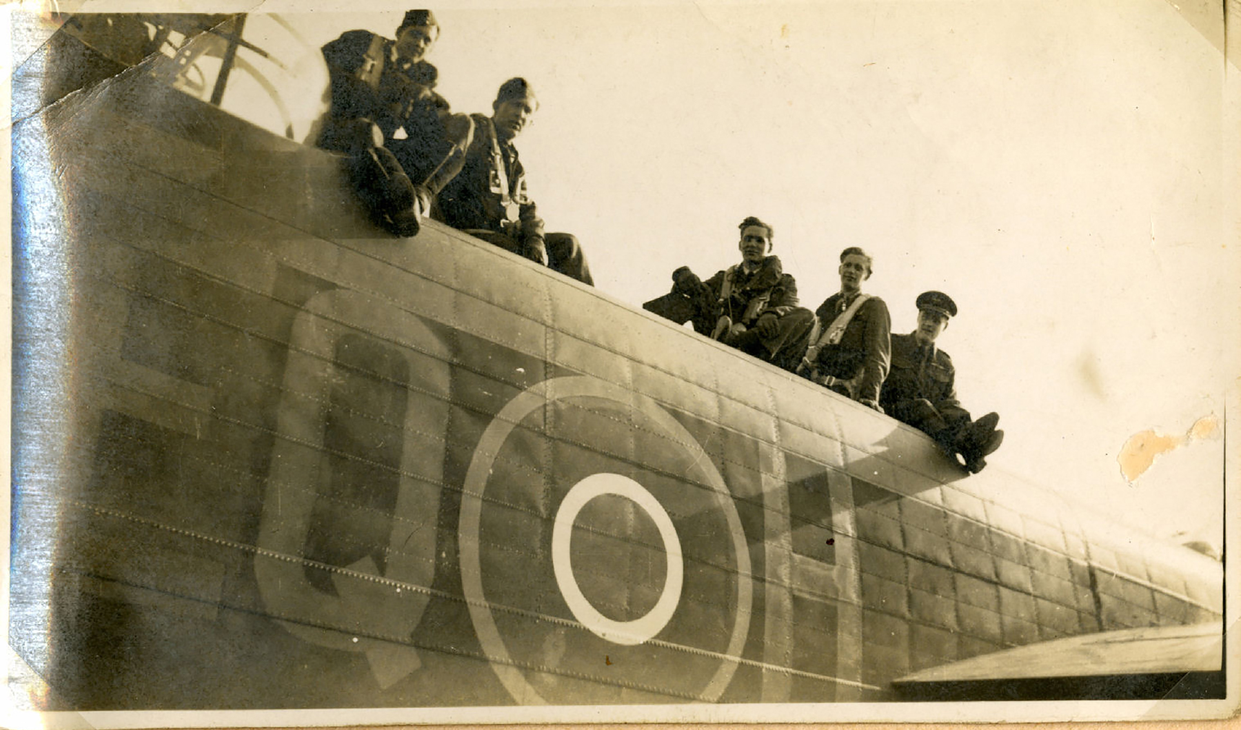 In a sepia-tone photograph, five men wearing old-style flight suits sit along the top of the fuselage behind the cockpit of a vintage aircraft.