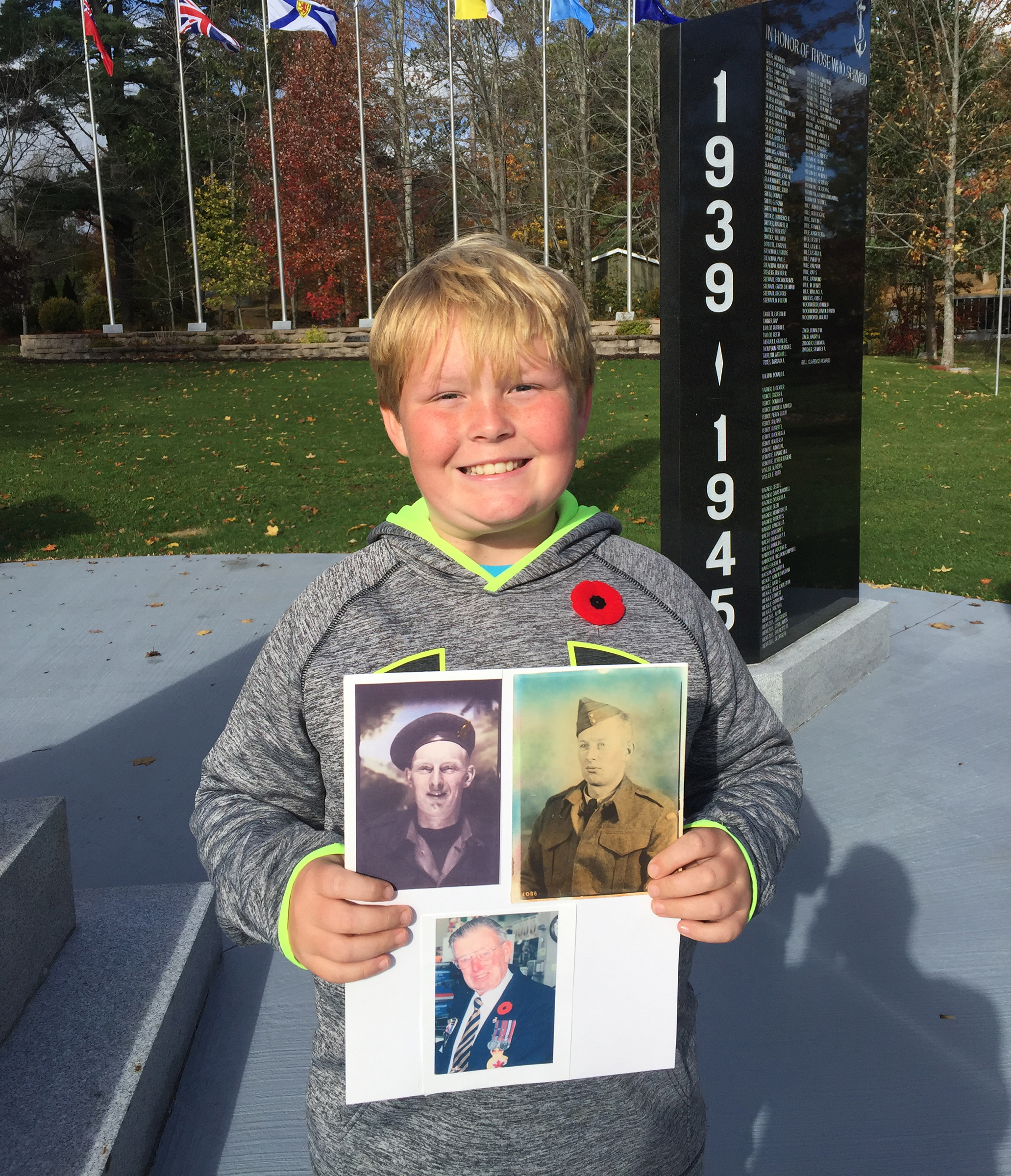 A child stands in front of a black granite cenotaph, holding a poster with three photos affixed to it.