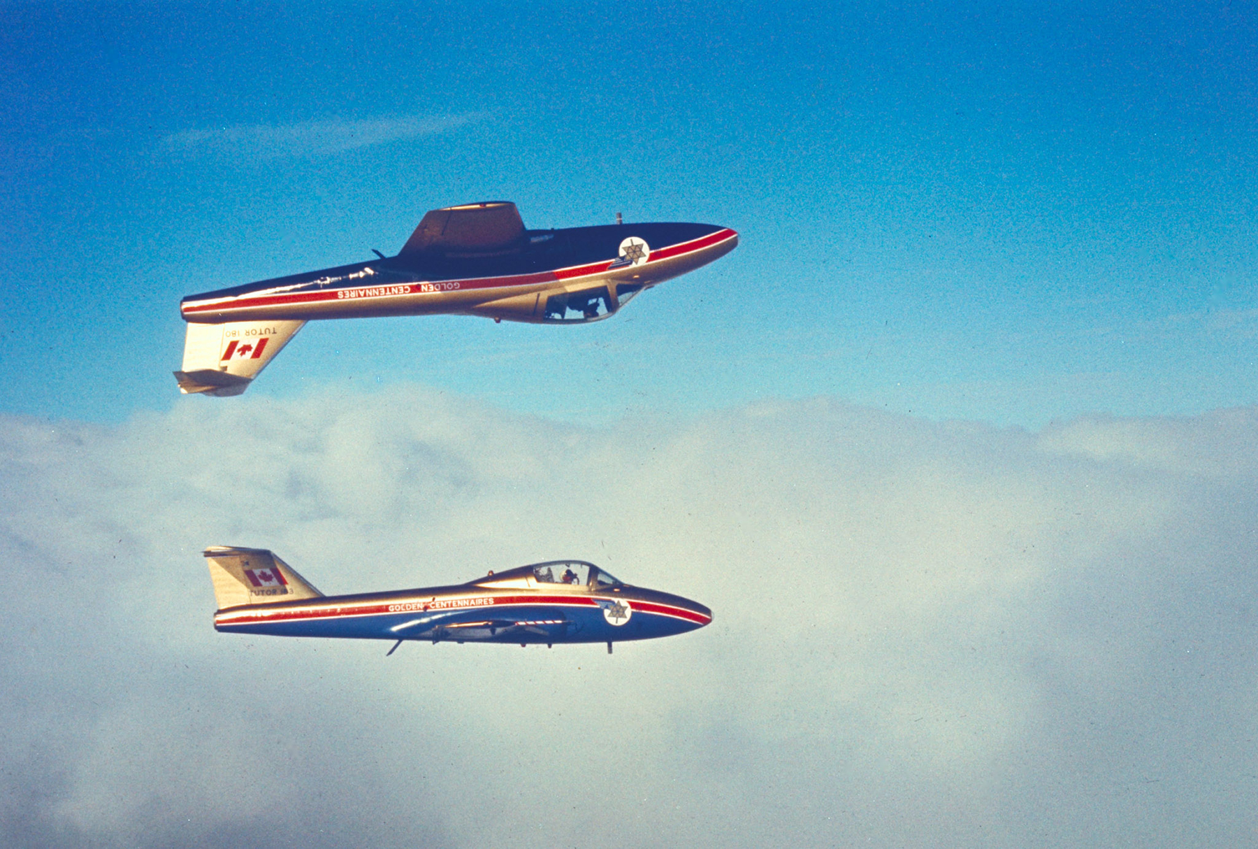 At first glance, Golden Centennaire CT-114 Tutor aircraft appear to fly one directly above the other in an undated air-to-air photograph. In fact, there is a carefully predetermined amount of lateral separation between them as well. PHOTO: DND Archives, RNC-1589-11