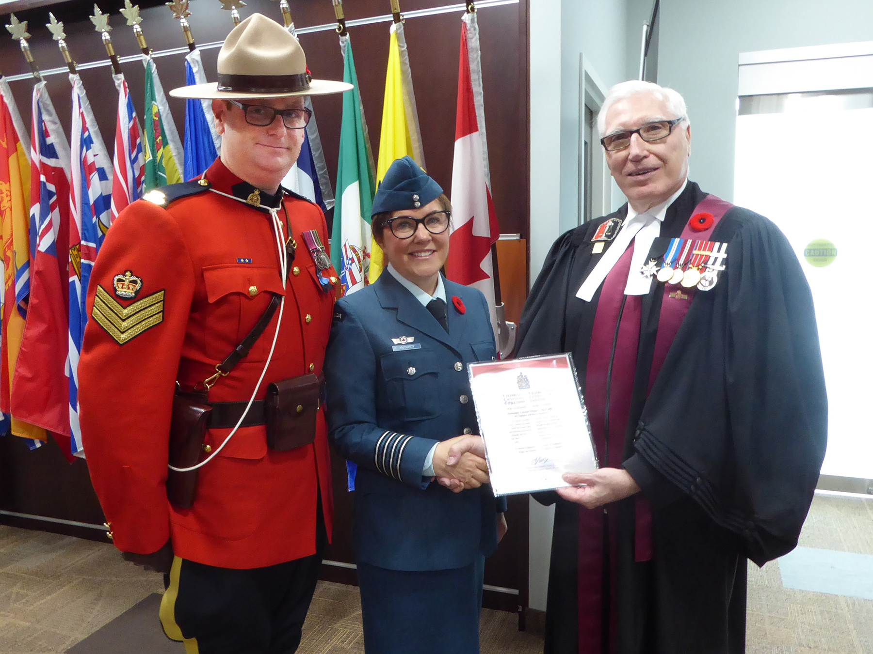 In front of flags, a man in a black ceremonial robe with medals gives a document to a woman in a blue dress uniform as a man wearing a red uniform jacket, black pants and a wide-brimmed hat watches.
