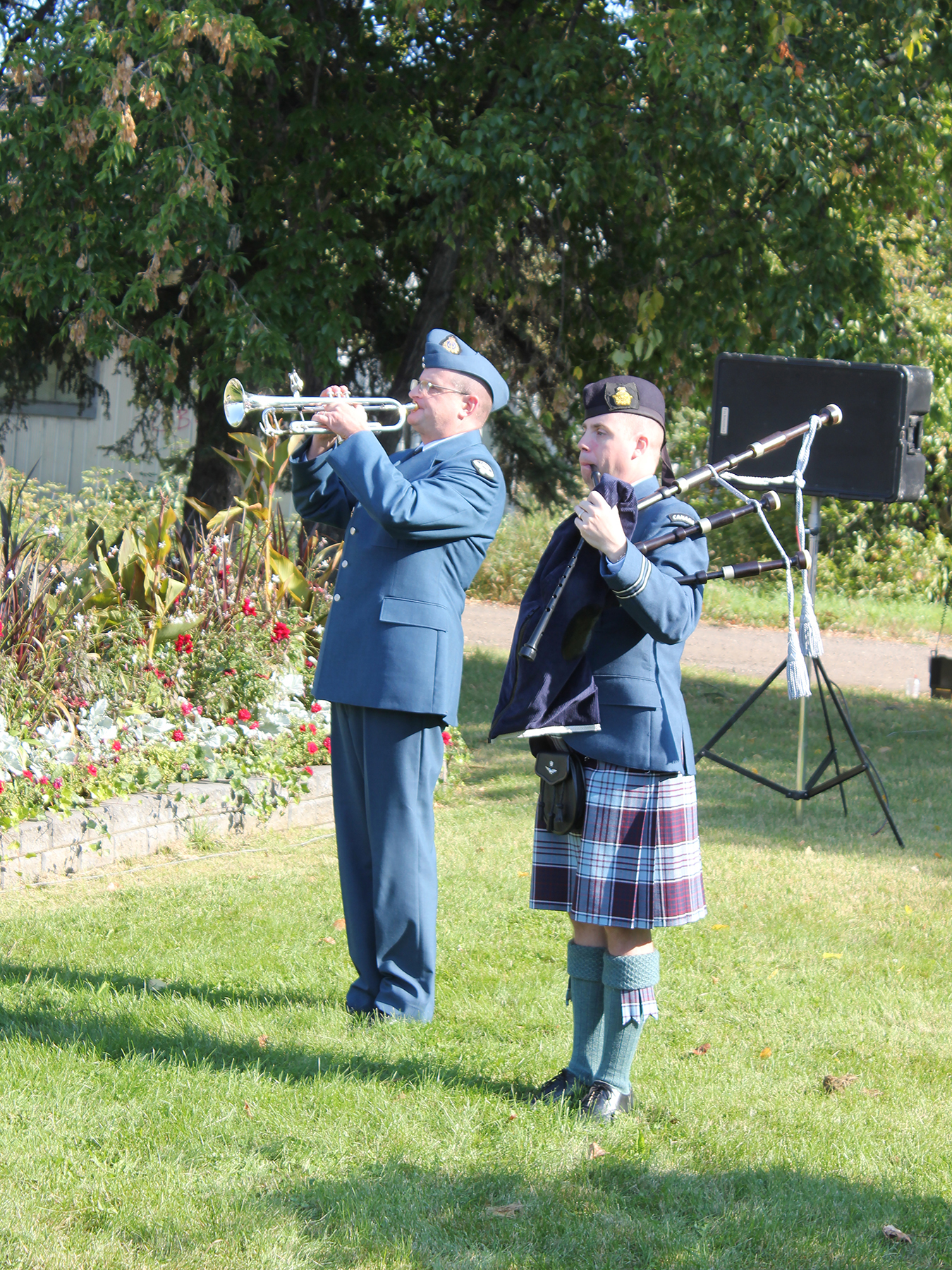 "Todd Farrell, a civilian volunteer trumpeter with the 4 Wing Band, sounds ""Last Post"" during the 2017 Battle of Britain ceremony in Cold Lake, Alberta, as piper Captain James Bezanson, a 4 Wing air traffic controller, stands at rest. PHOTO: Jeff Gaye"