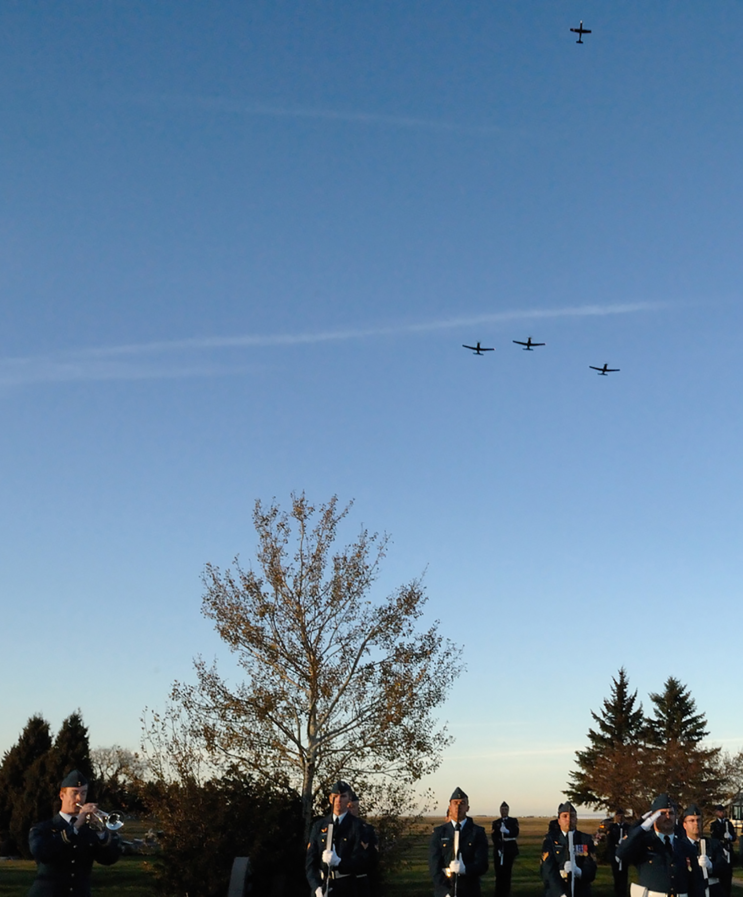 "Trumpeter Lieutenant Patrick Trembath, of 4 Wing Cold Lake, Alberta, sounds ""Last Post"" as CT-156 Harvard II aircraft fly the ""Missing Man Formation"" over a ceremony on October 17, 2008, in Rosedale Cemetery in Moose Jaw, Saskatchewan, marking the death of RCAF Snowbird pilot Captain Bryan ""Mav"" Mitchell of 15 Wing, who died when his CT-114 Tutor aircraft crashed on October 9, 2008. PHOTO: Sergeant Denis Gauthier, WG2008-0413-24"