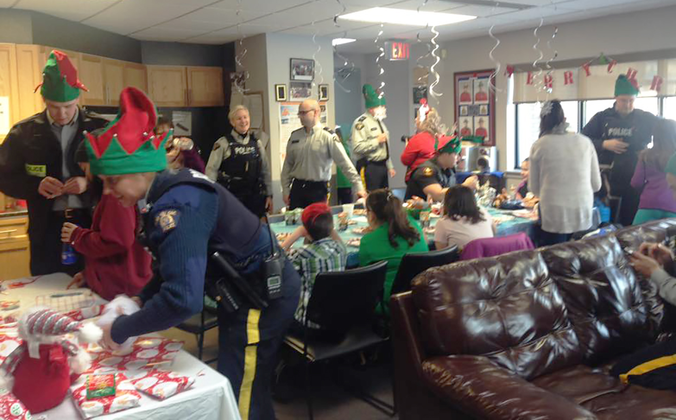 Le détachement de la Gendarmerie royale du Canada de Happy Valley-Goose Bay grouille d'activité pendant le rassemblement de jeunes, de bénévoles et de lutins à l'occasion de la journée « Shop with a Cop », le 3 décembre 2017. PHOTO : https://www.facebook.com/hvgbCrimePrevention/