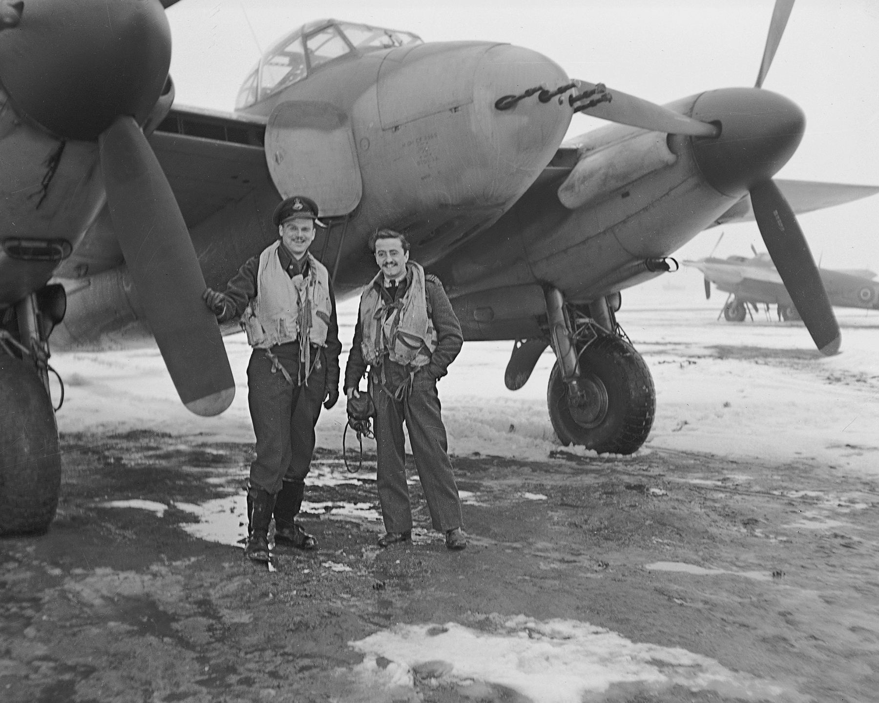 "First time out in their new Mosquito—and on New Year's night in the bargain—this twosome from RCAF 406 ""Lynx"" Squadron celebrated by shooting down an ME.110. Flight Lieutenant Bill Boak (left) a navigator from Saskatoon, Saskatchewan, spotted their target over an enemy aerodrome, and Flight Lieutenant Phillip Etienne, a pilot from Montreal, Québec, did the rest with several cannon bursts. It was their first ""kill"" but they were just getting nicely started on their tour, it being their fifth mission. Flight Lieutenant Boak figures he has tallied one for his hometown, which has adopted the squadron. PHOTO: DND Archives, PL-42217"