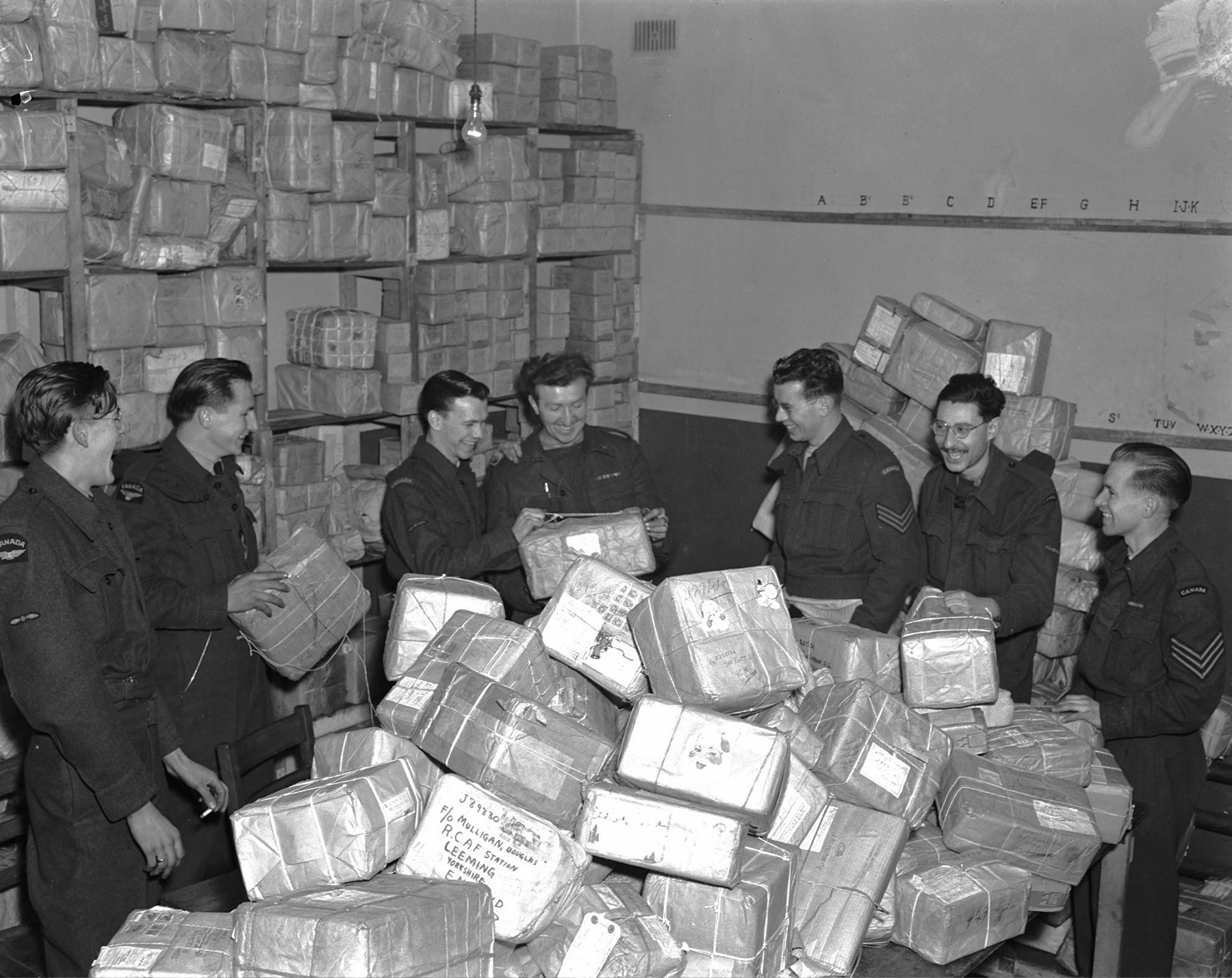 Christmas never means holidays in wartime, and certainly not for these postmen at RAF Leeming in England, surrounded by Yuletide mail that has arrived from Canada. They will work far into the night to make sure that every member of the RCAF receives mail from home. PHOTO: DND Archives, PL-46607