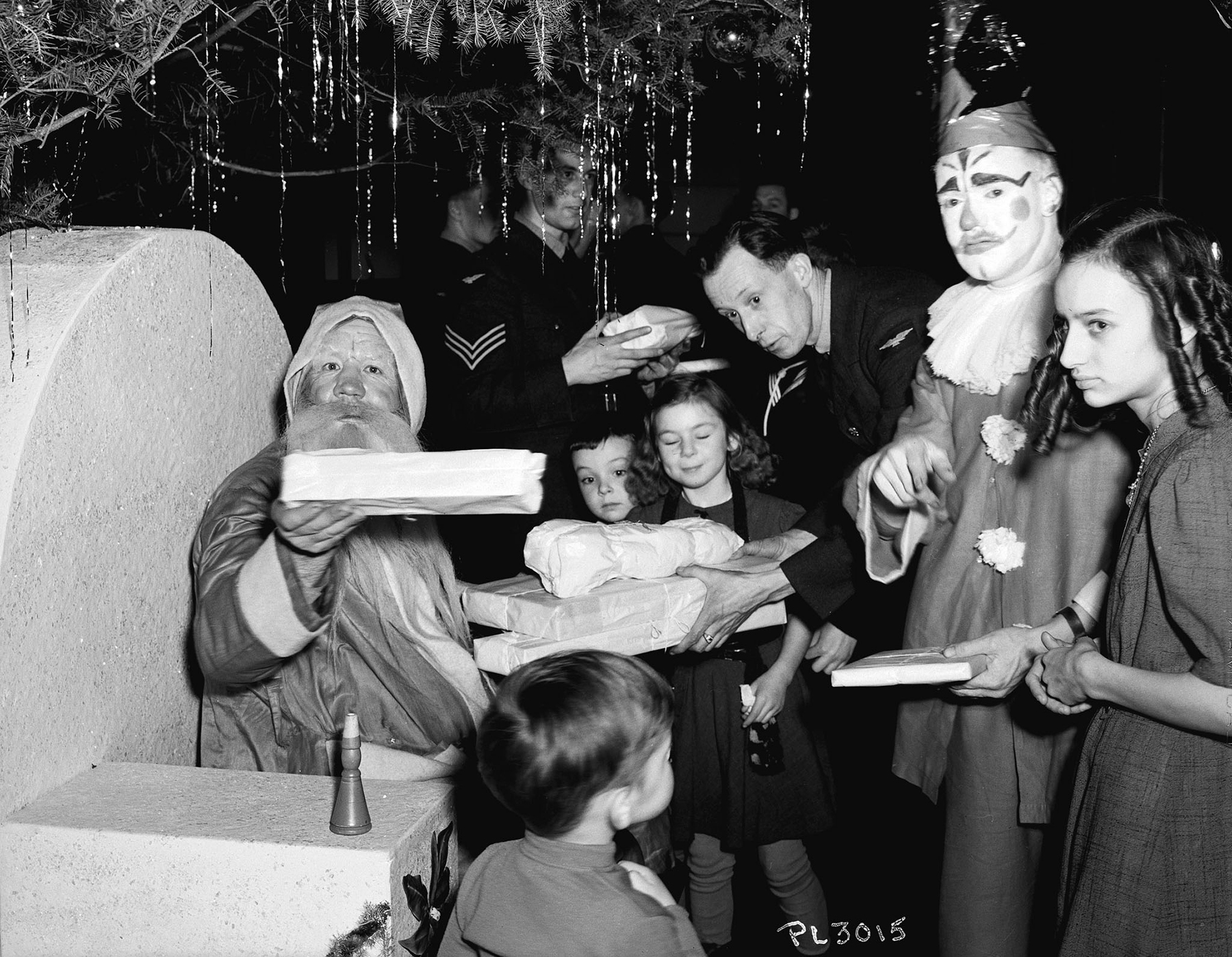 The line comes to an abrupt stop as Santa offers a gift to the photographer during the December 20, 1940, Children's Christmas Party thrown by Royal Canadian Air Force personnel at RCAF Station Rockcliffe, just east of Ottawa, Ontario. PHOTO: DND Archives, PL-3015