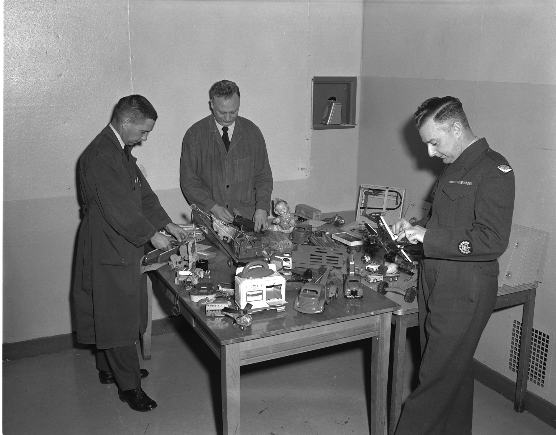 Warrant Officer H.F. Gerow (right) inspects some of the toys that personnel of the Safety Equipment School at RCAF Station Aylmer, Ontario, including Corporal Len Graham and Corporal Jack Parkhill, have been making or repairing during their spare time. The toys will be distributed to children of the Protestant Orphans' Home in London, Ontario, as Christmas presents. PHOTO: DND Archives, PL-94298