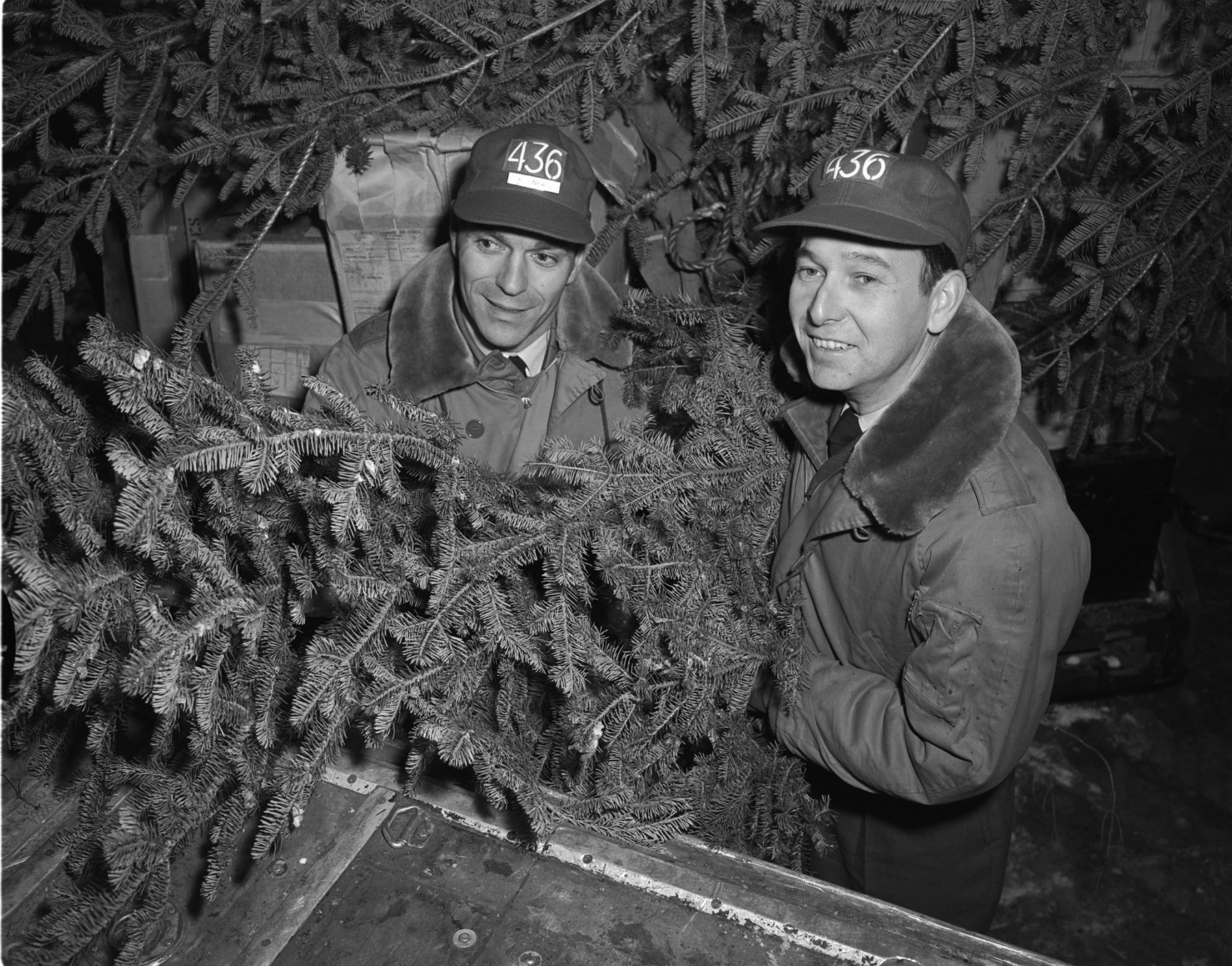 Flight Lieutenant H. Newin (left) and Flying Officer W. Empringham, deep in fir trees but not in a forest, are winging northward on board an RCAF CC-119 Flying Boxcar. The two members of Air Transport Command are engaged in Operation Santa Claus, dropping mail and Christmas trees to Canada's northern outposts. Because of the long Arctic nights, the bundles drift down by parachute under a bright moon, helping the people below to see the falling shapes. Flight Lieutenant Newin and Flying Officer Empringham are members of 436 Lachine Squadron, one of two Flying Boxcar squadrons participating in Operation Santa Claus. PHOTO: DND Archives, PL-86283