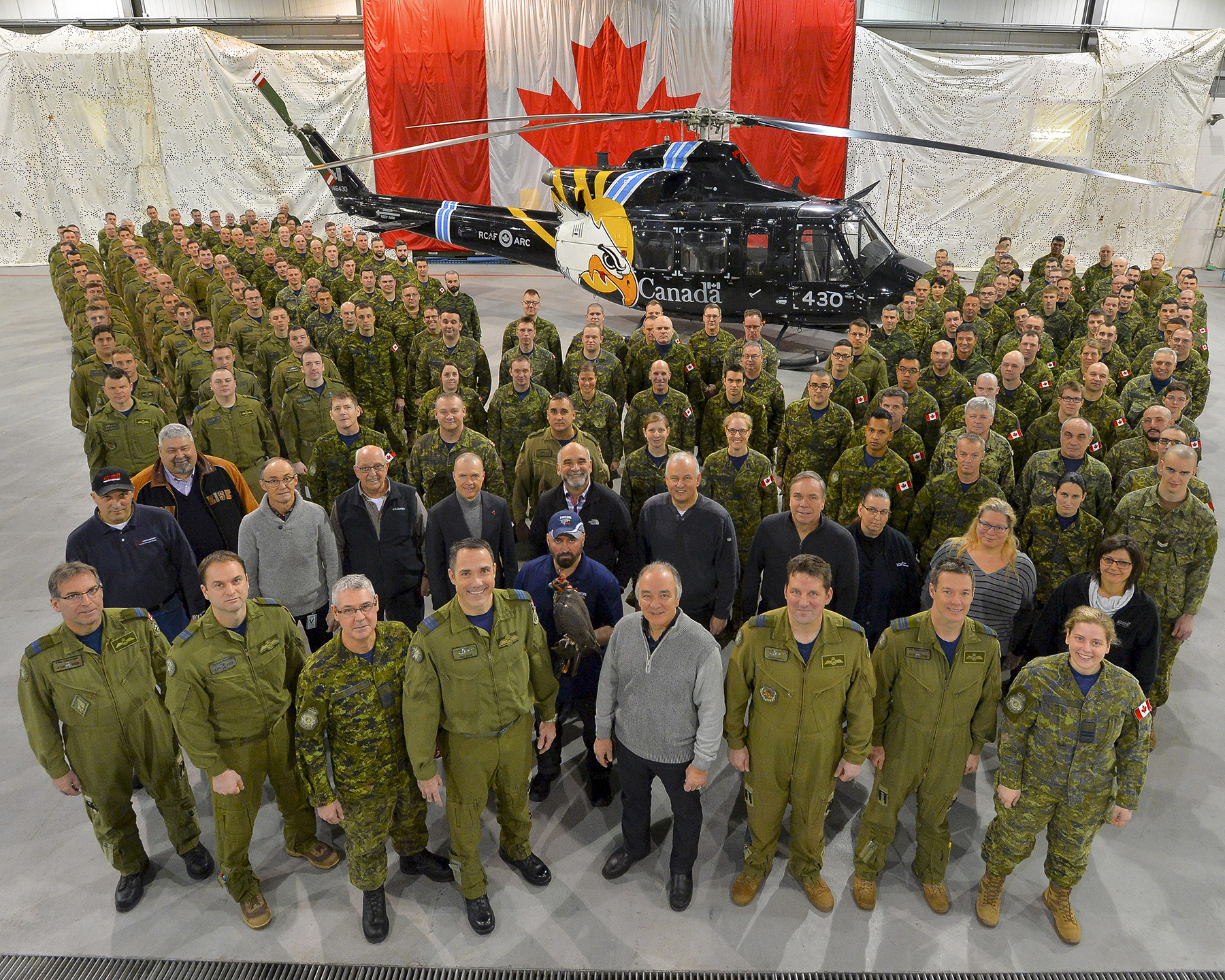 The full complement of 430 Squadron personnel—aircrew, groundcrew, maintainers, civilian staff, gyrfalcon and others—gather for a squadron 75th anniversary portrait in front of a CH-146 Griffon helicopter emblazoned with a gyrfalcon head, which also appears on the 430 badge. PHOTO: DND, VH2018-001-002
