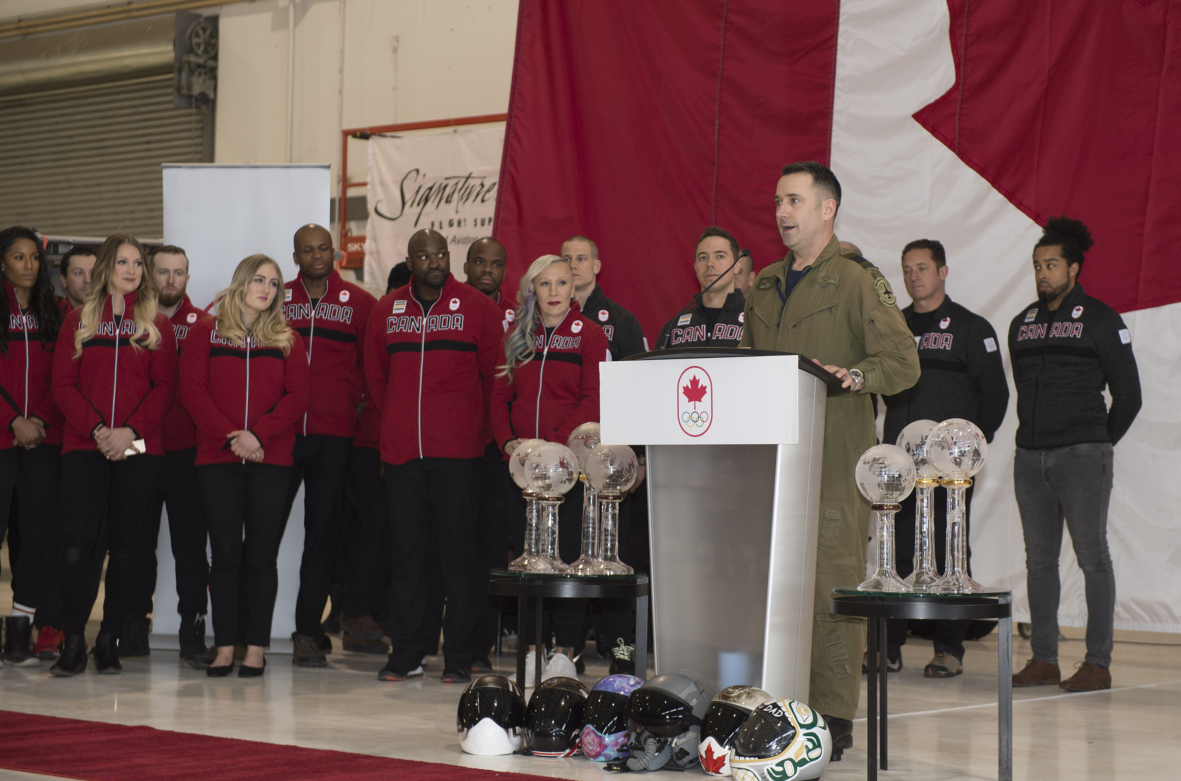 "Lieutenant-Colonel Colin Marks, commanding officer of 419 Tactical Fighter Training Squadron at 4 Wing Cold Lake, Alberta, speaks to members of Canada's 2018 Olympic Bobsleigh and Skeleton Team in Calgary, Alberta, on January 24, 2018 during the official nomination of the team and the unveiling of the 2018 Olympic sled design. ""We have many things in common,"" he told them. ""We are all trying to achieve our mission for Canada. All of our service members know that the RCAF is built upon teamwork. For us the difference between mission success and mission failure really is the strength of our team and our members. The same can be said for all of you today."" PHOTO: Ordinary Seaman Justin Spinello, CK03-2018-0012-004"