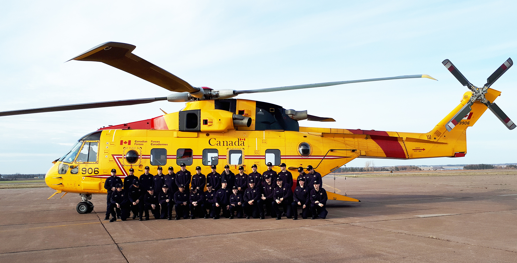 "During ""Boat Camp"", held in part at Summerside Airport in Summerside, Prince Edward Island, firefighting cadets from Holland College in Charlottetown pose beside a CH-149 Cormorant from 413 Transport and Rescue Squadron after touring the helicopter on November 22, 2017. PHOTO: Submitted"
