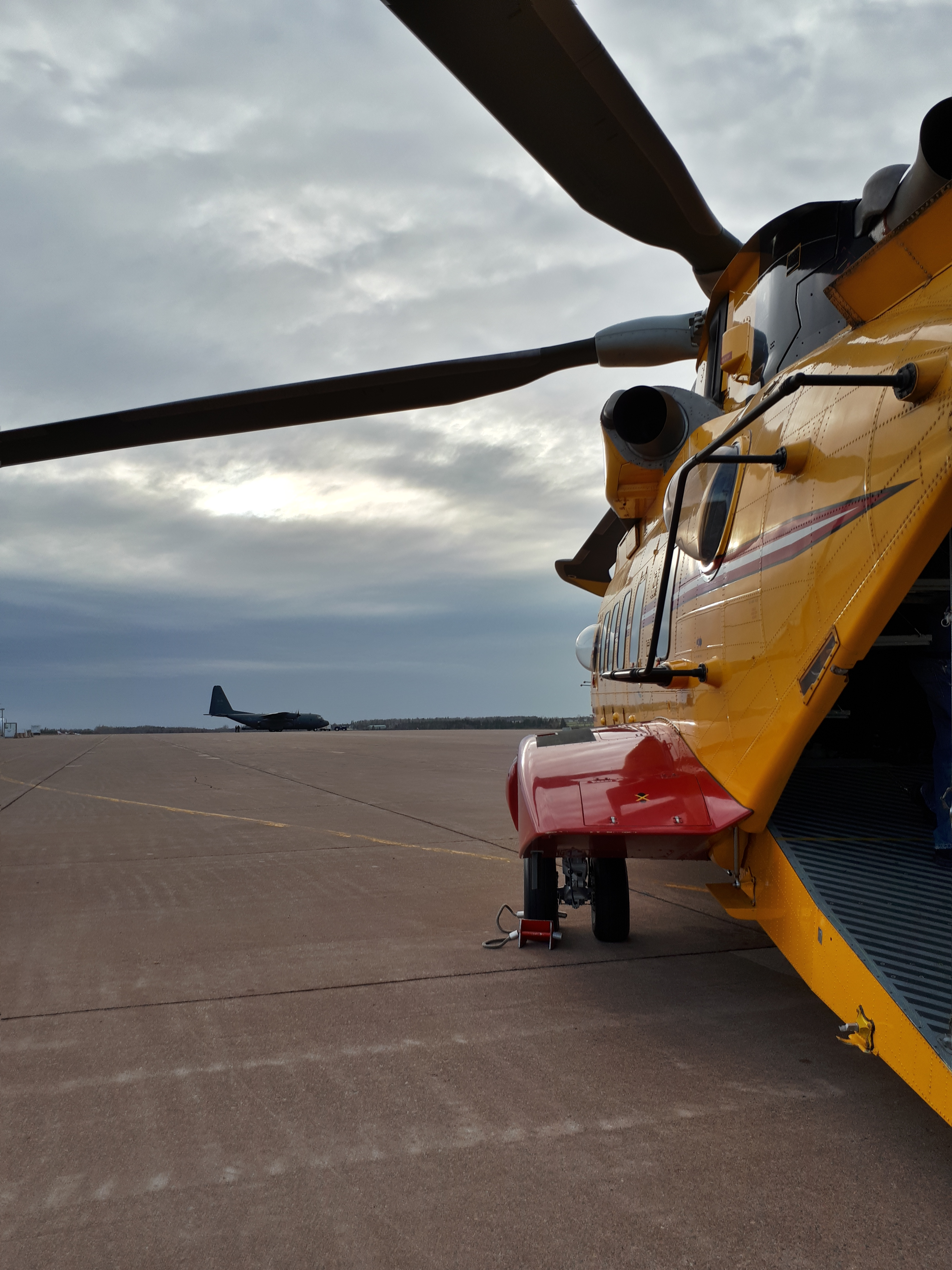 "At Summerside Airport in Summerside, Prince Edward Island, on November 22, 2017, a CH-149 Cormorant helicopter (foreground) from 413 Transport and Rescue Squadron, and a CC-130 Hercules cargo aircraft wait on the tarmac between training scenarios during ""Boat Camp"". PHOTO: Submitted"