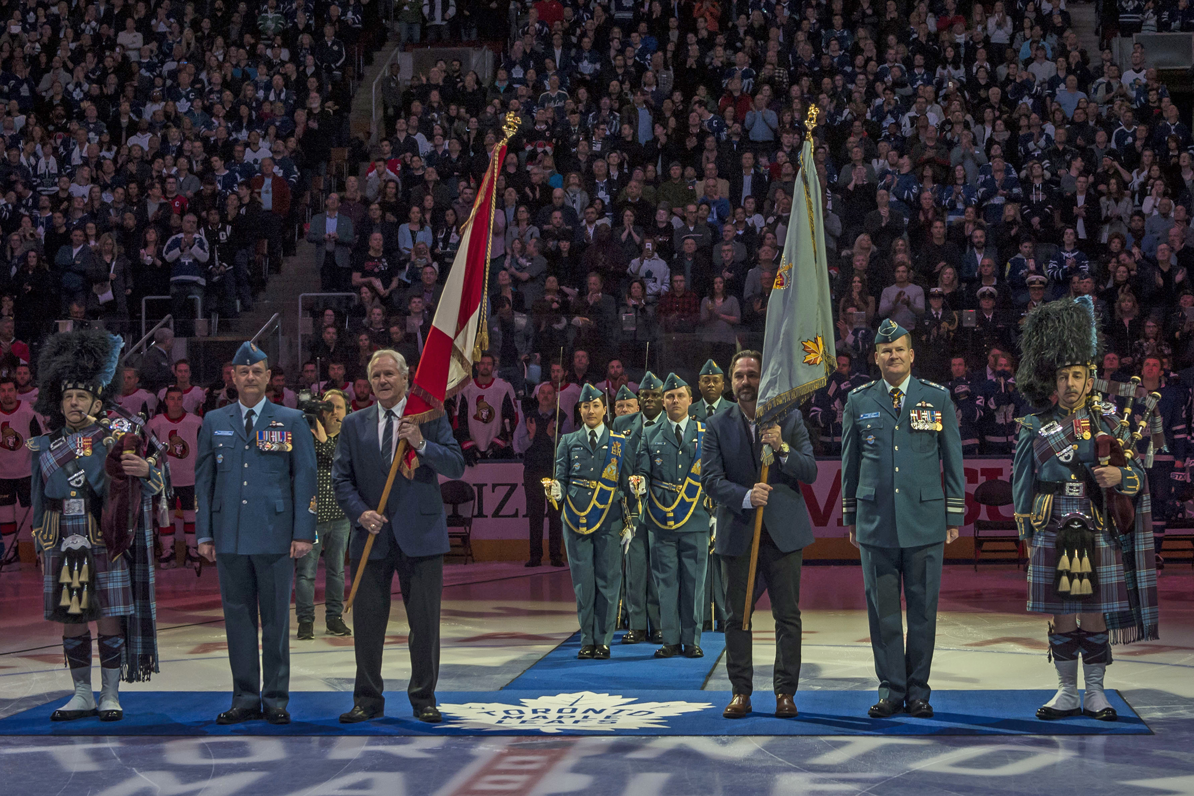 Four people in military uniforms and two in civilian clothing, each holding a large flag on a pole, stand on the surface of a hockey arena with a large crowd behind them.