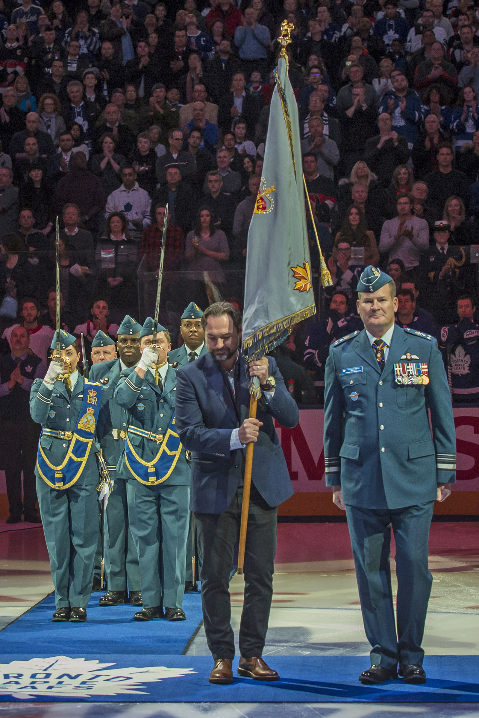 Leafs' alumni Darcy Tucker, holding the retired Air Command Colour, stands beside Lieutenant-General Mike Hood, commander of the Royal Canadian Air Force. PHOTO: Corporal Alana Morin, FA03-2018-0015-004
