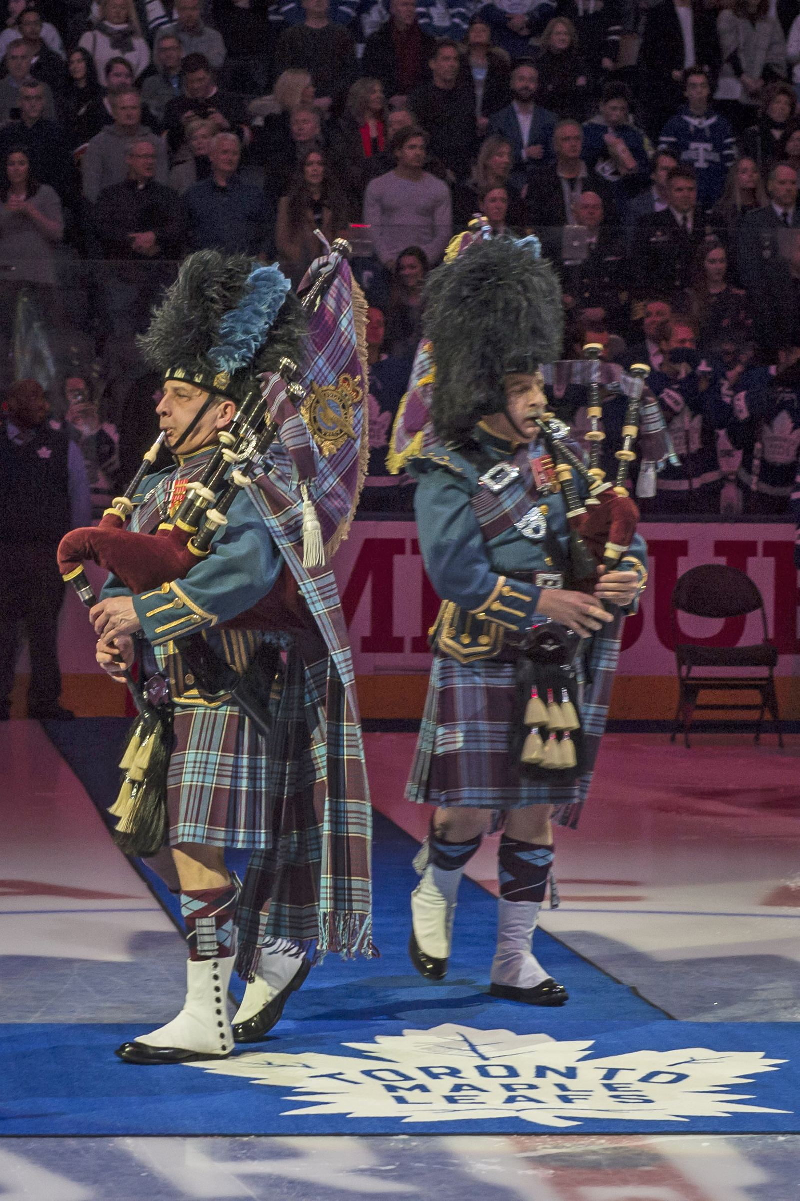Lieutenant-Colonel (retired) Kenneth J. Mackenzie and Major Allan J. MacKenzie, brothers and members of the RCAF Pipes and Drums, lead RCAF members and Maple Leafs' alumni on to the ice at the Air Canada Centre in Toronto on February 10, 2018, for the ceremony transferring the custody of the RCAF's retired Colours to the Maple Leafs' hockey team. PHOTO: Corporal Alana Morin, FA03-2018-0015-005