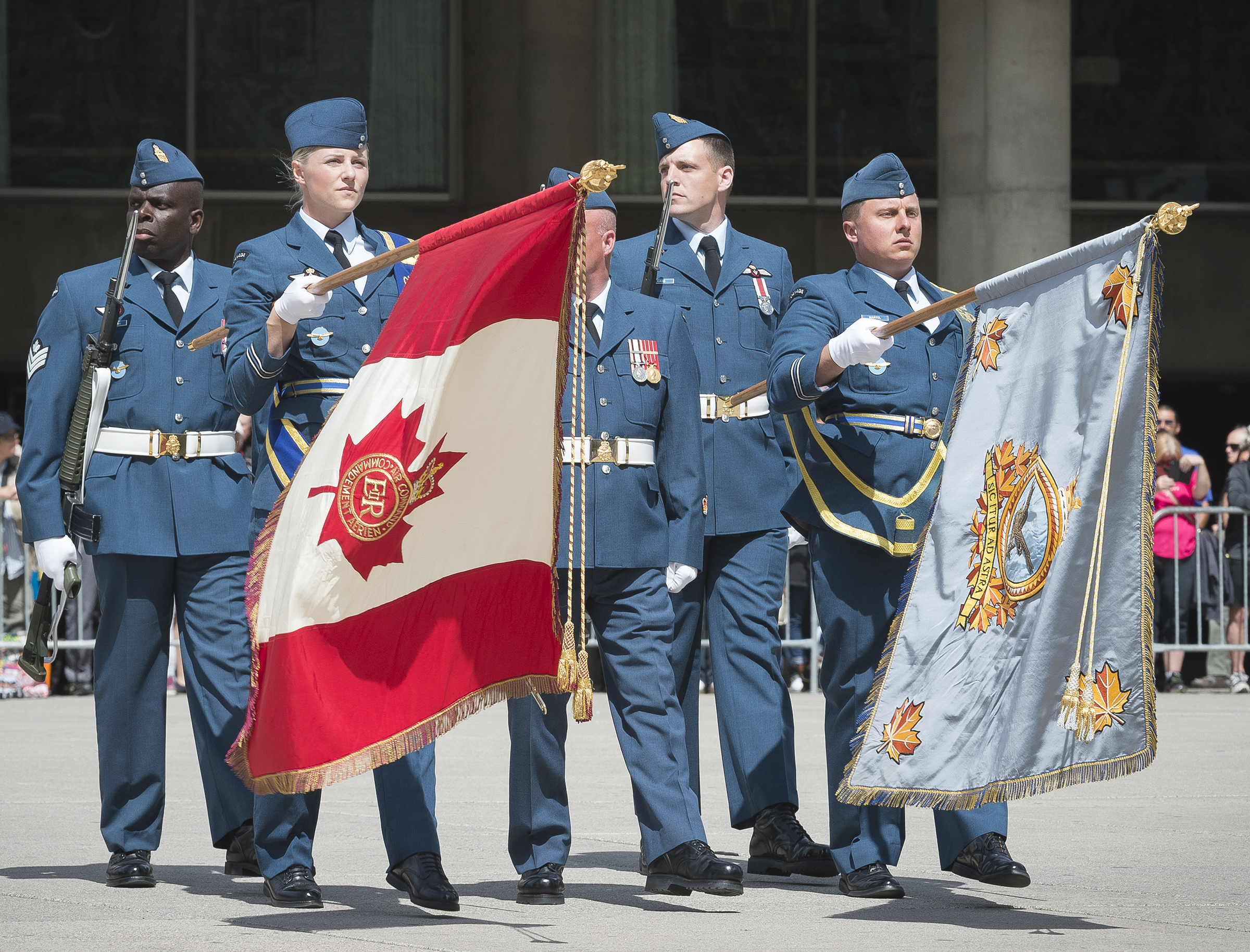Several people wearing blue RCAF uniforms march together. Two are carrying flags with the staffs of the flags held horizontally.