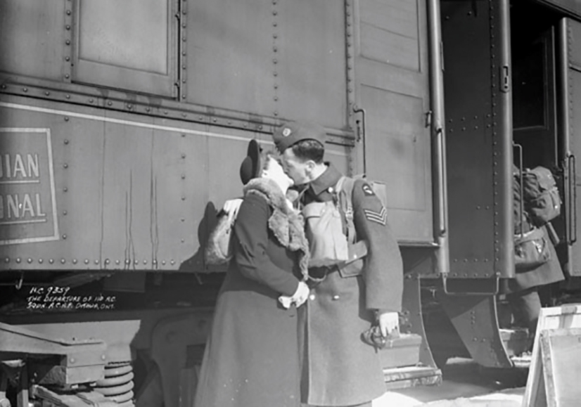 In a vintage photograph, a man and woman kiss beside a train.