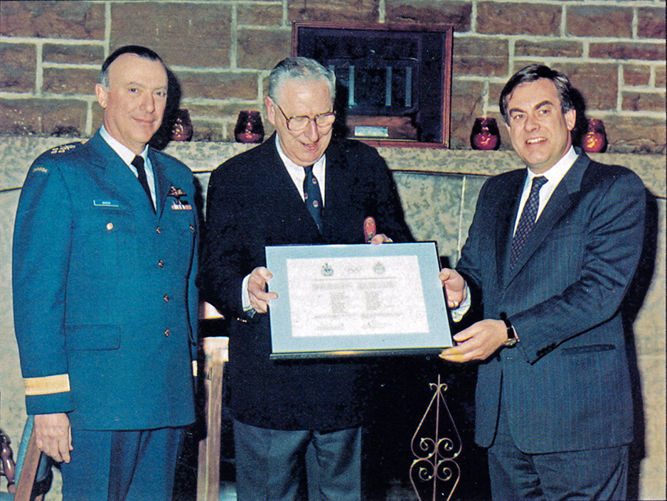 Three men, one in a military uniform, stand beside each other. The man in the centre and on the right hold a framed certificate between them.