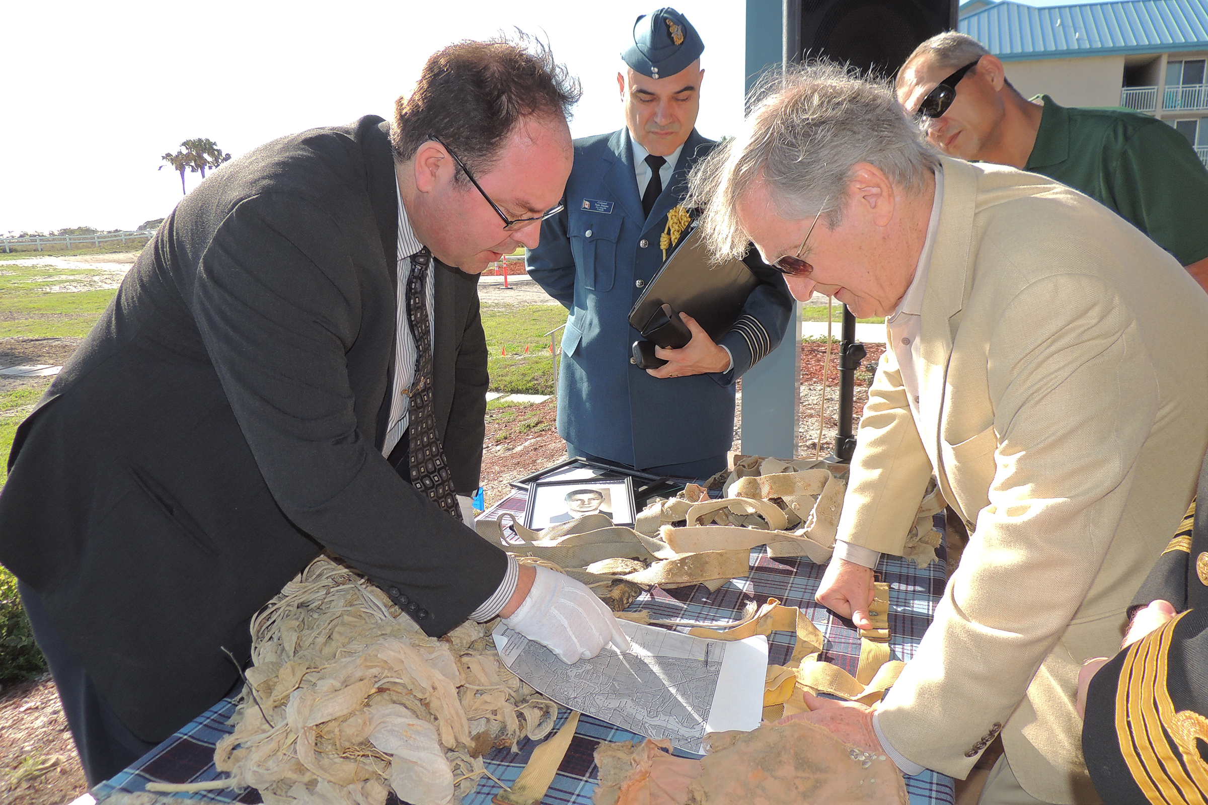 Dr Richard Mayne (left), the RCAF's senior historian, explains the flight path that Lieutenant Barry Troy was on when he disappeared off the coast of Florida on February 25, 1958, to Lieutenant Troy's brother, Dick Troy, who was only 21 when his brother vanished. On the table are the artifacts recovered on a Jacksonville beach, not far from the crash site, last autumn. Looking on are Colonel Tom Dunne (centre), Canadian air attaché at the Embassy of Canada in Washington, DC, and Zach Johnson, the Jacksonville park ranger who discovered the artifacts and realized their significance. PHOTO: Joanna Calder, RCAF public affairs
